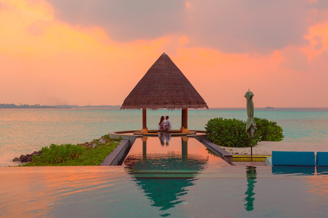 Couple Under Hut Beside Sea and Infinity Pool