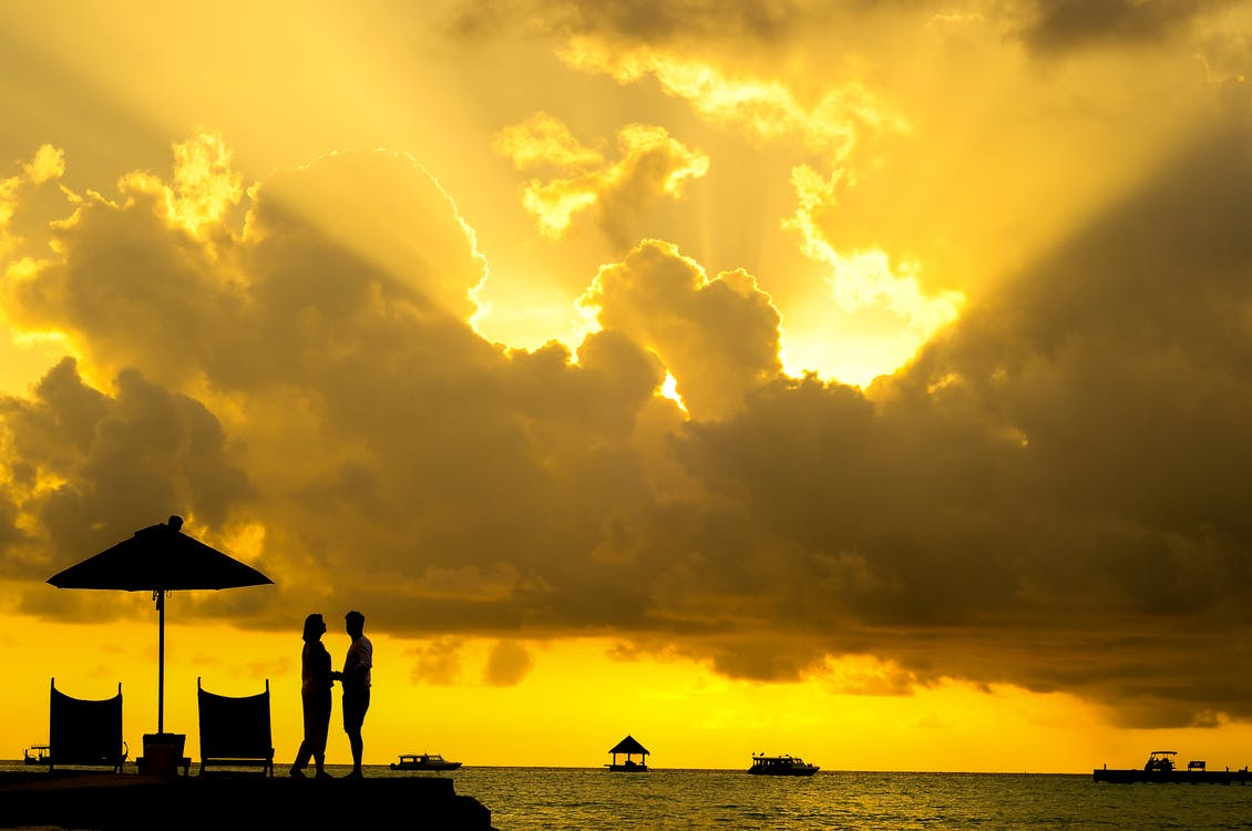 Silhouette Photo of Man and Woman Beside Body of Water during Sunset