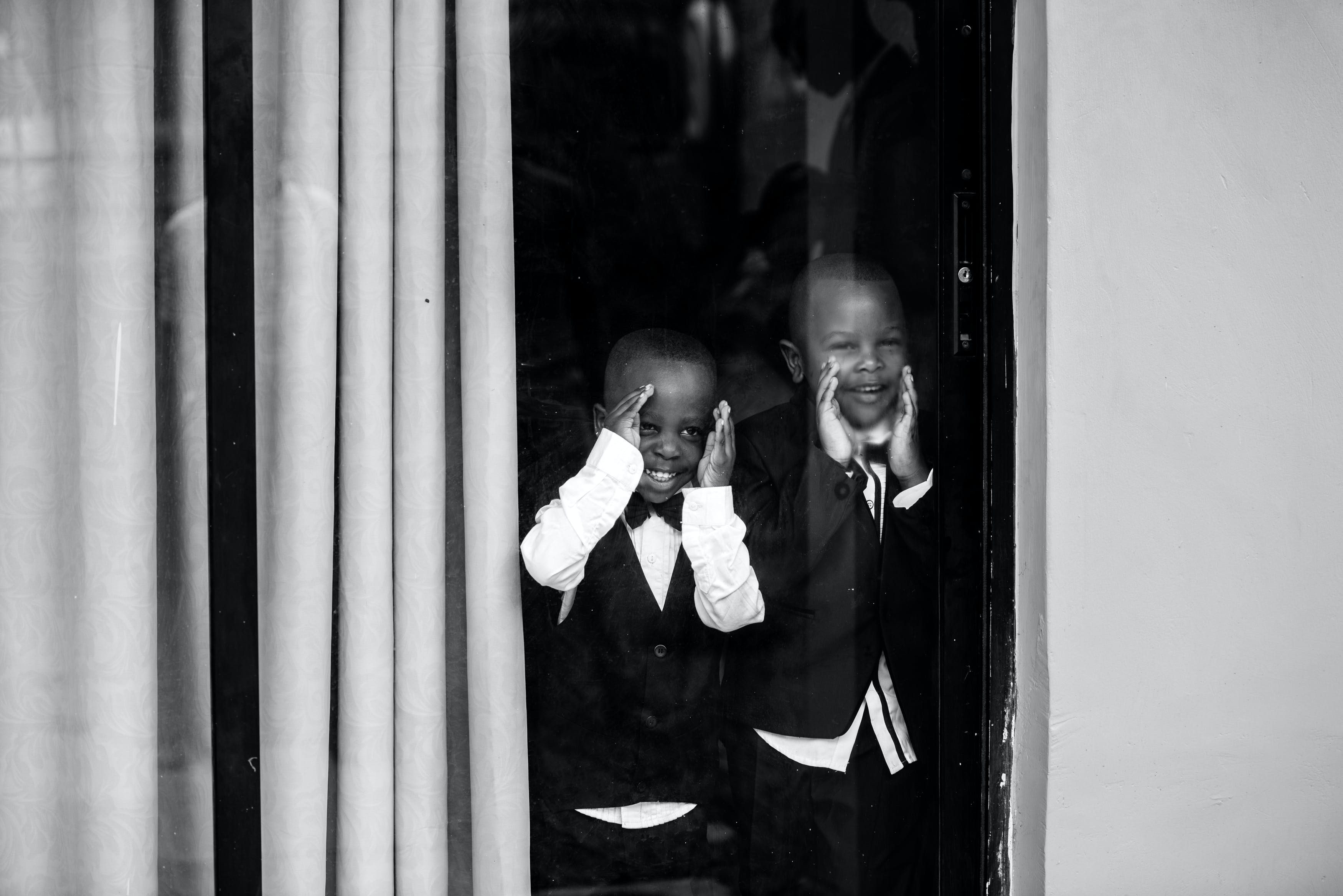 Two Boys in Front of Glass Window