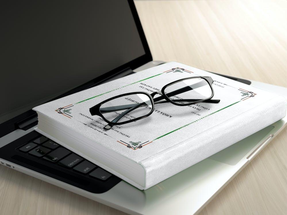 Black Frame Eyeglasses on White Book