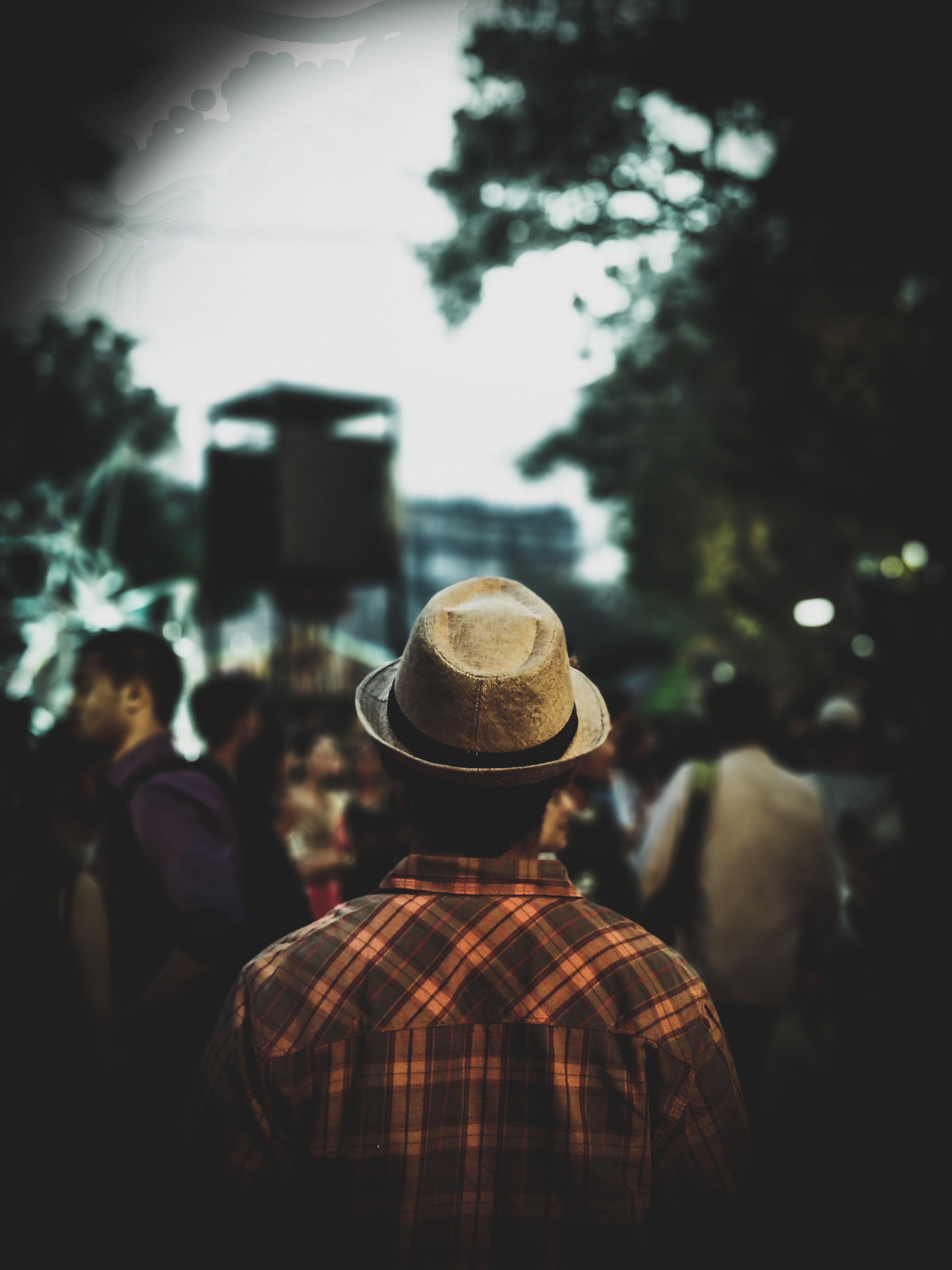 Man Wearing Fedora Hat and Plaid Shirt Facing People