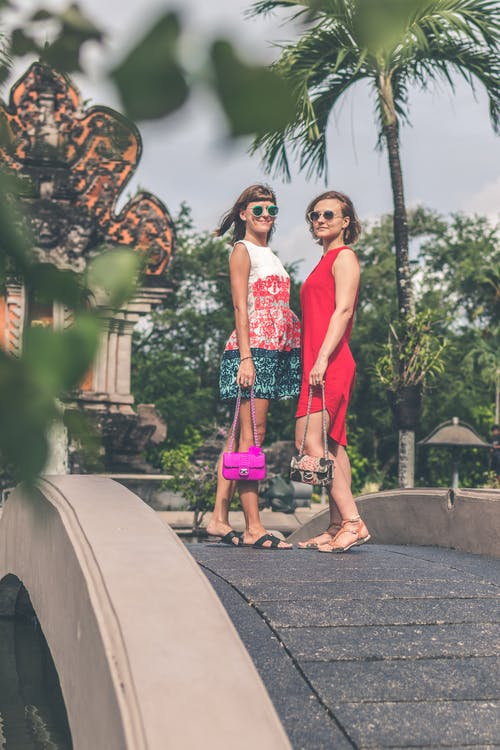 Two Women Wearing Sunglasses and Holding Bags Standing on Foot Bridge