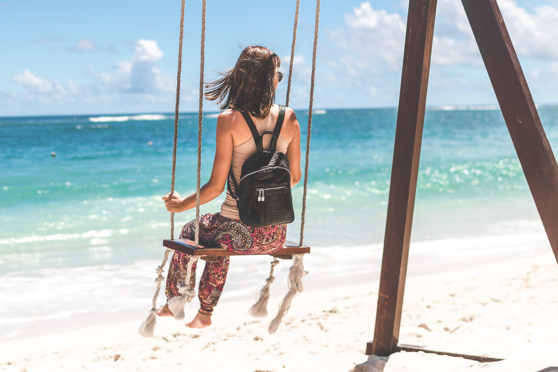 Woman Sitting on Seashore Swing