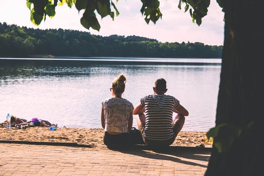 Woman in White Crop Top Besides Man in White and Black Stripes Shirt Beside Body Of Water