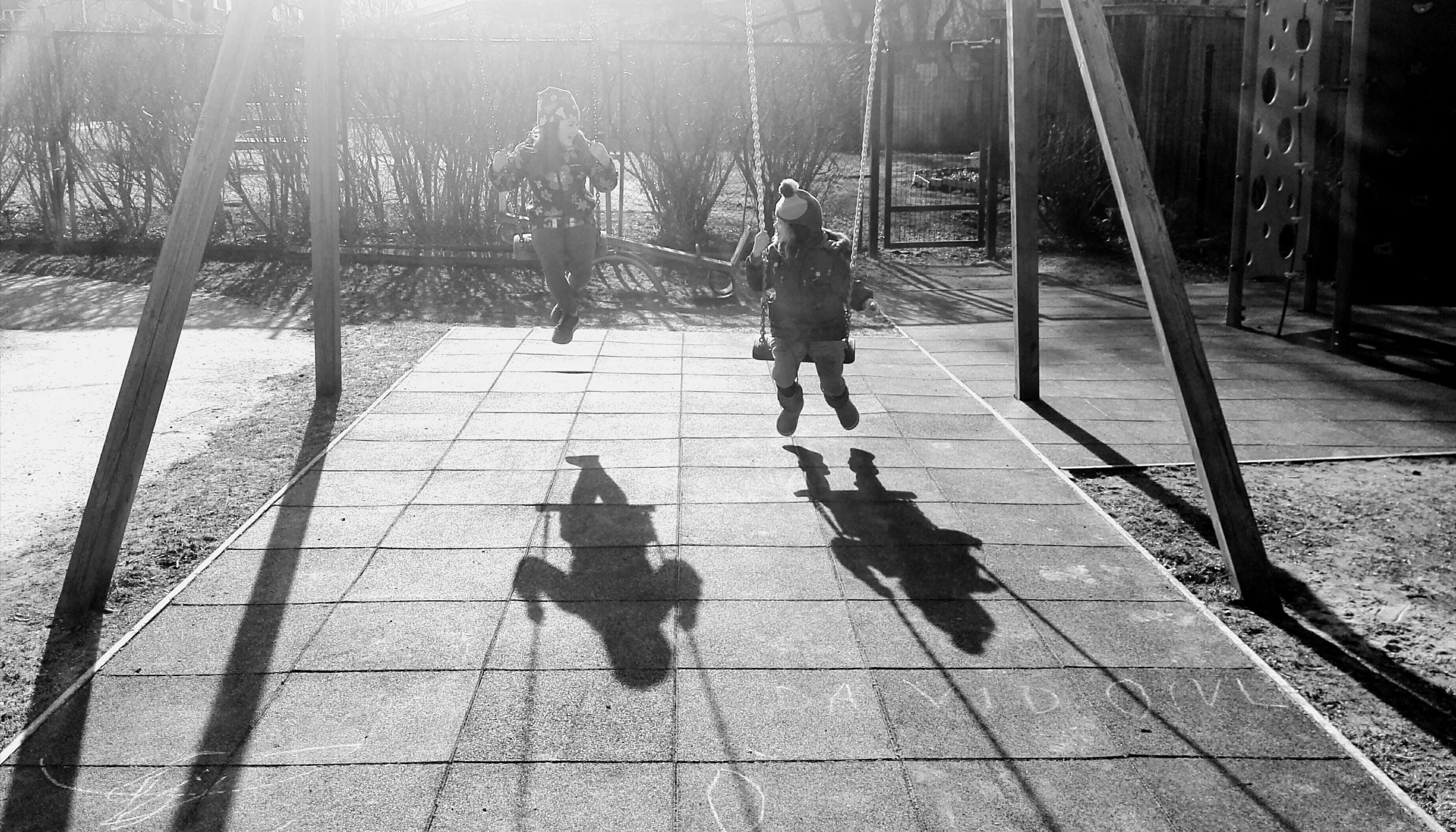 Monochrome Photography of Children On Swing
