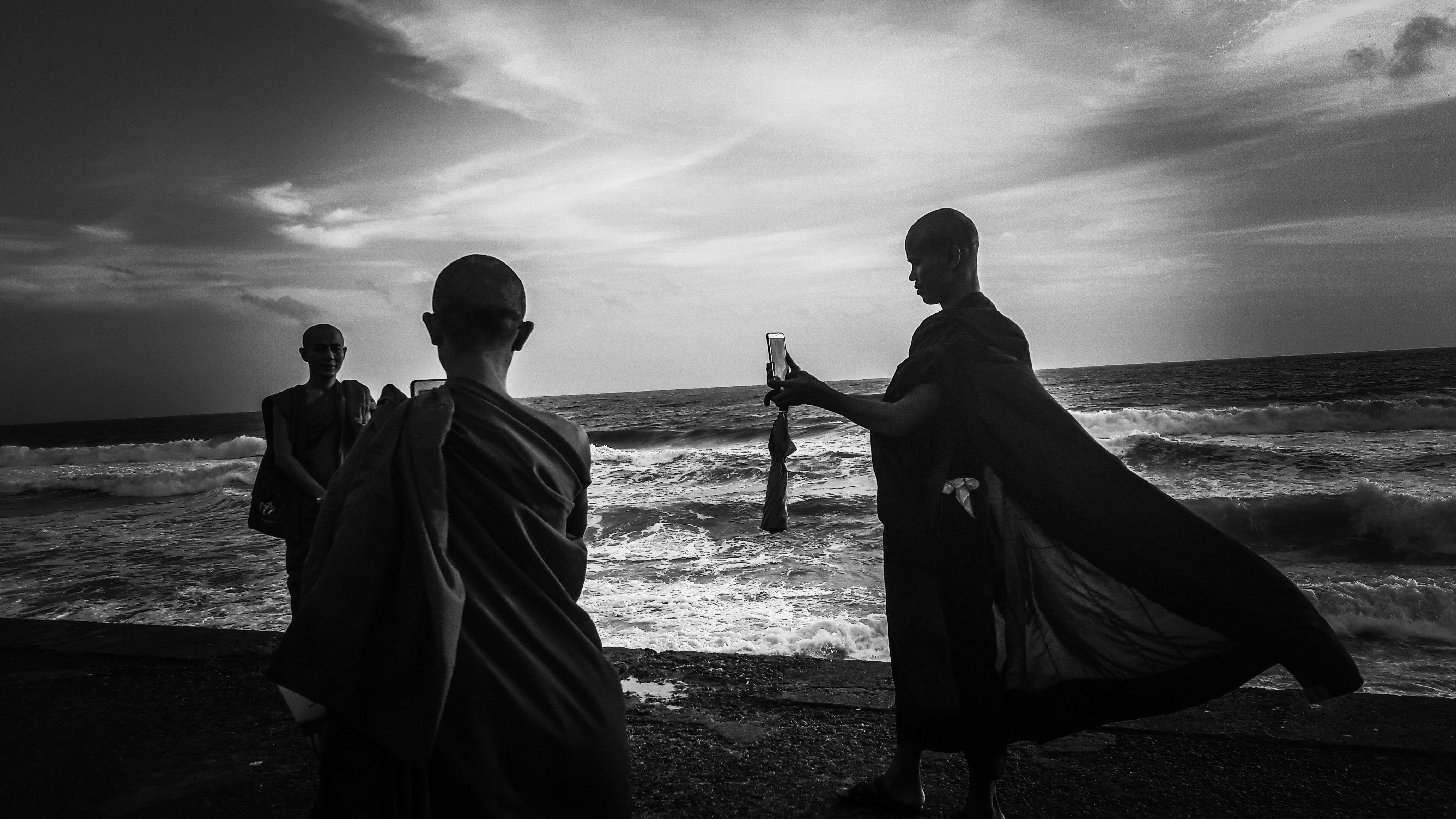 Greyscale Photography of Three Monks Near Ocean