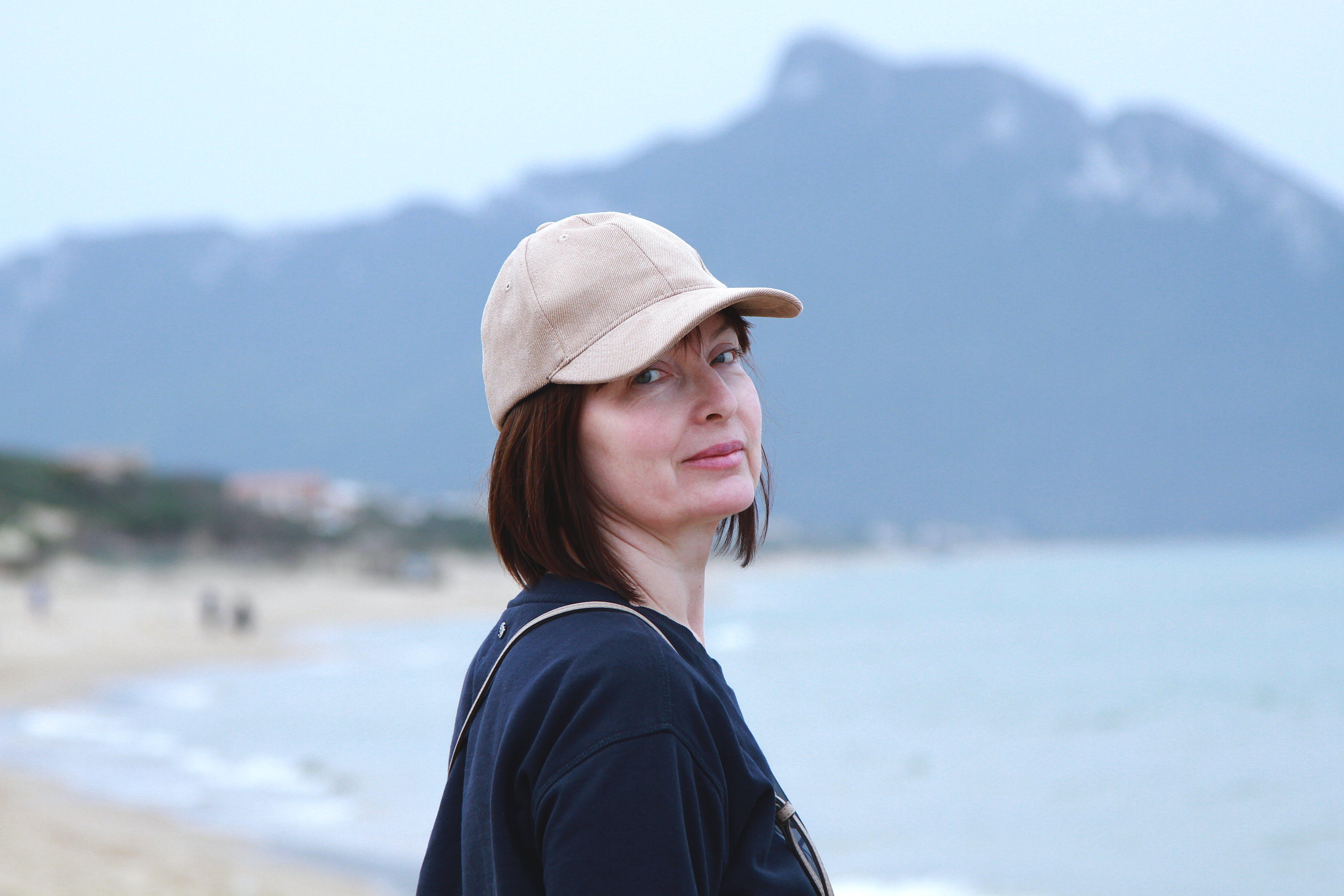 Woman Wearing Cap on Seashore Near Mountain