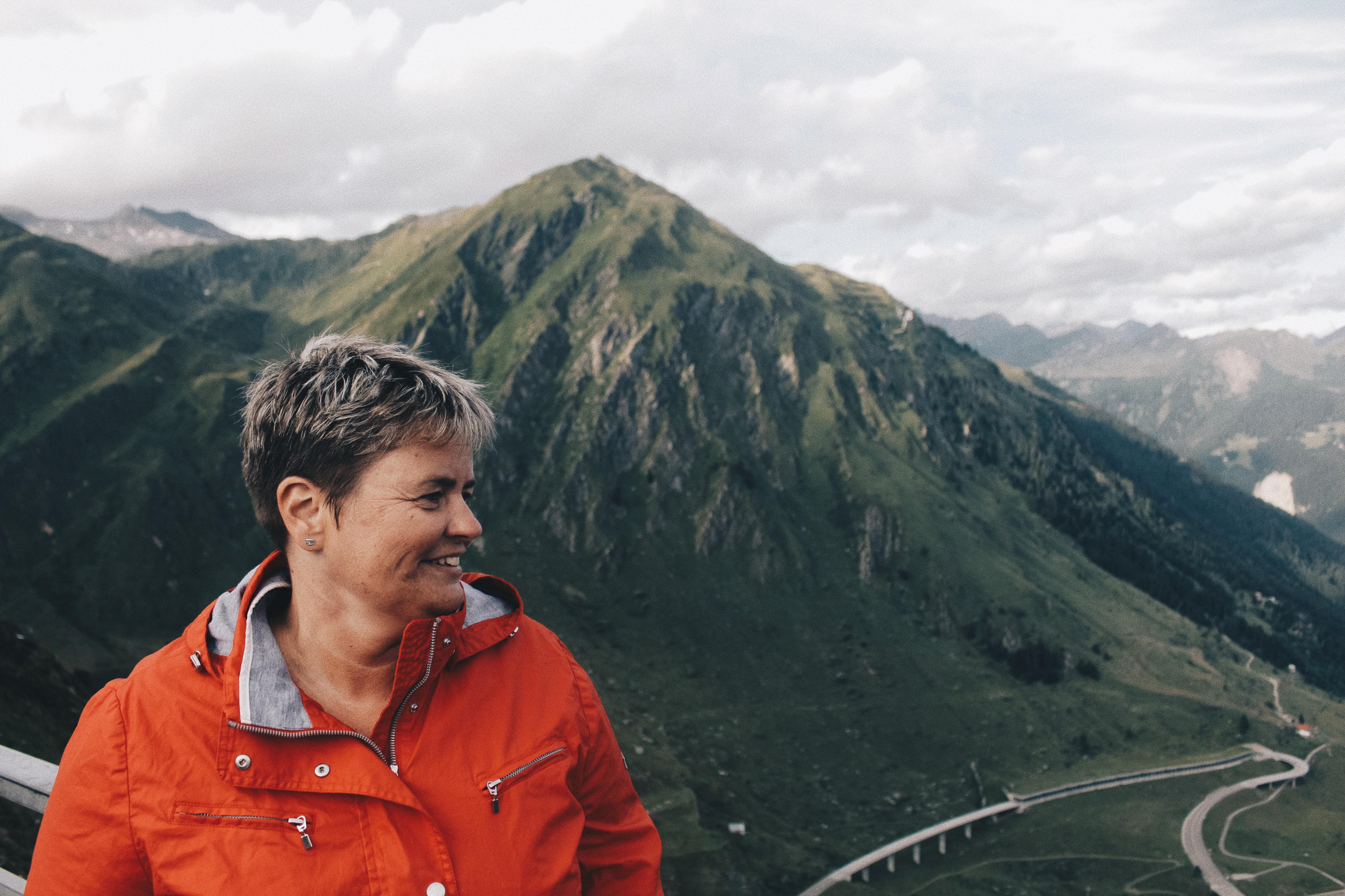 Person Wearing Windbreaker Jacket Standing Near on Mountain Range