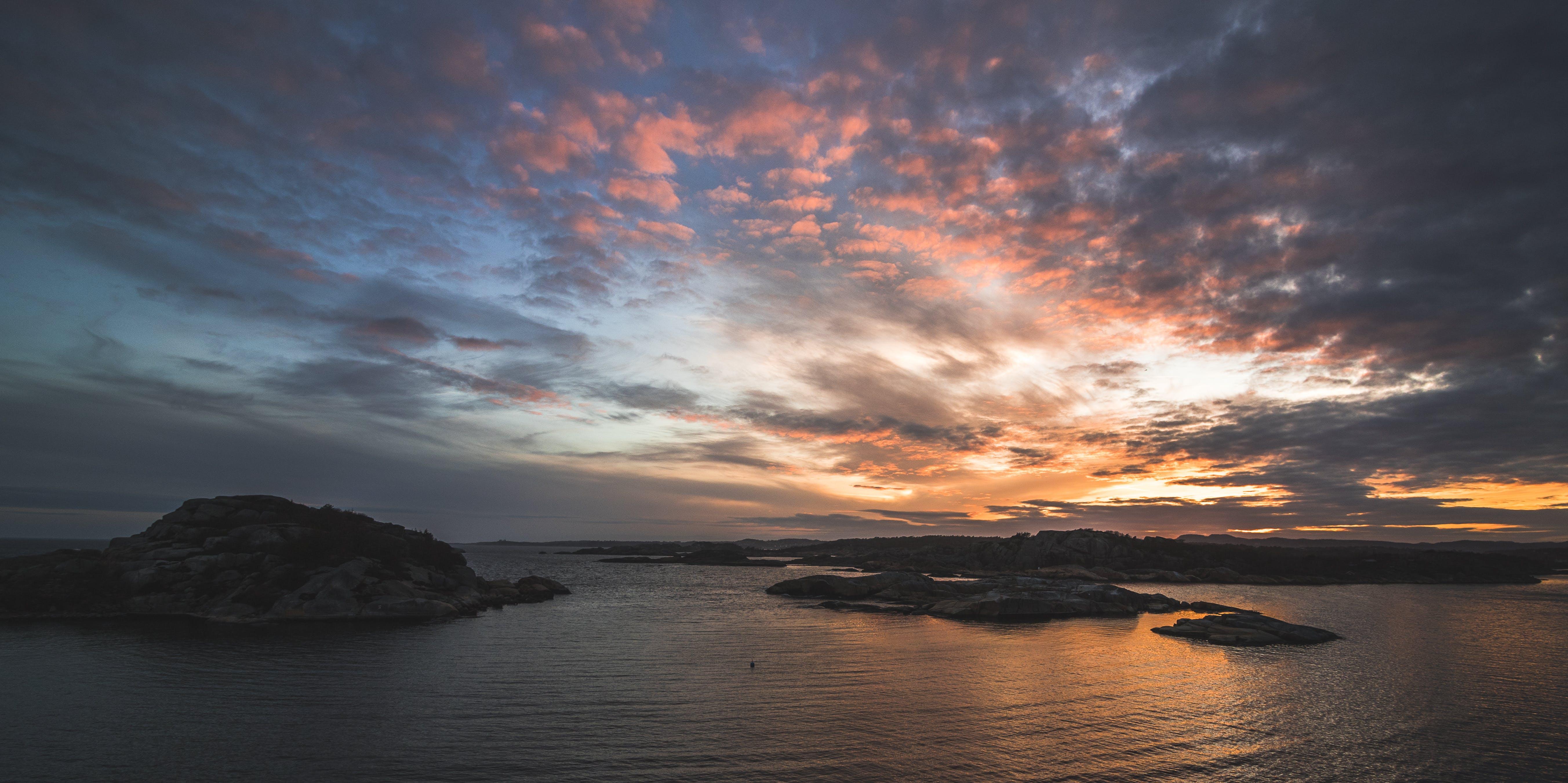 Body of Water Near Mountains Taken Under Orange Clouds during Sunset