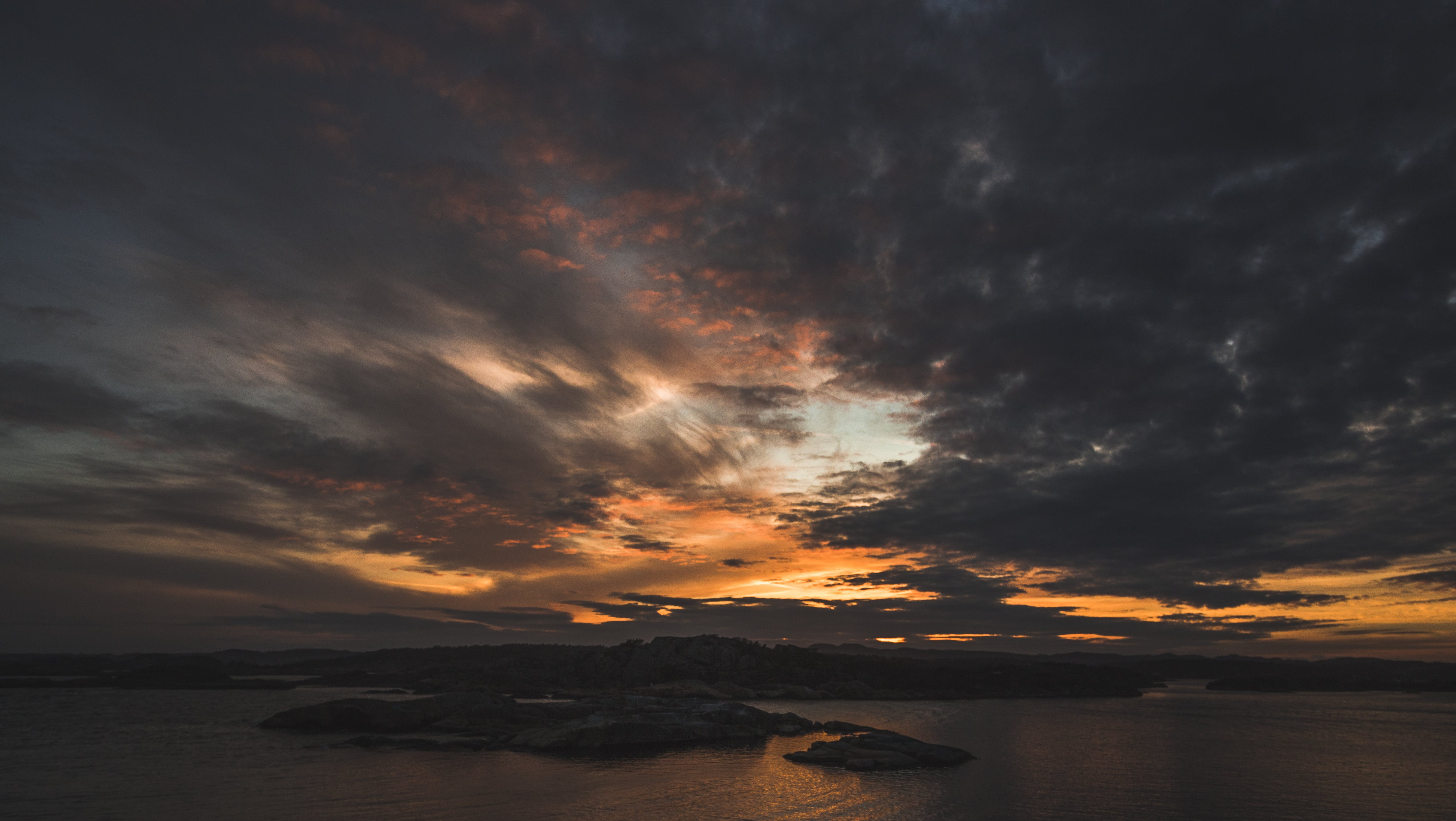 Silhouette of Island Under Grey Clouds during Golden Hour