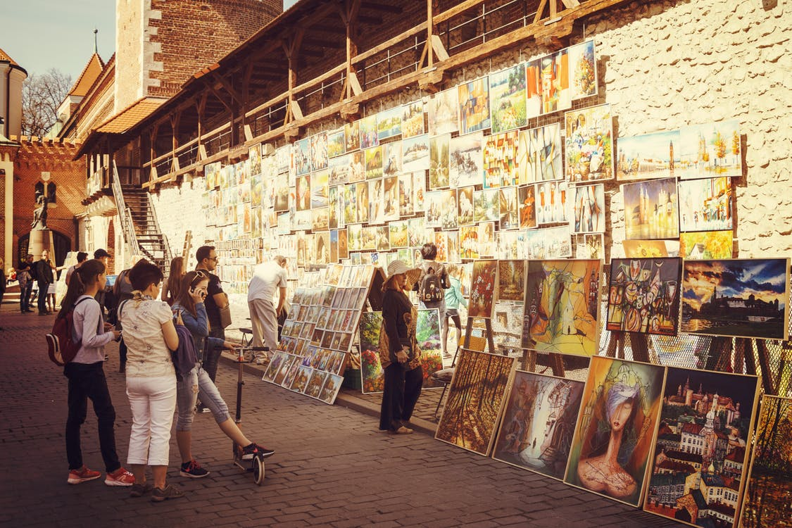 People Looking at Assorted-type Paintings