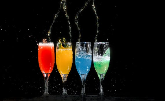 Four Champagne Flutes With Assorted-color Liquids