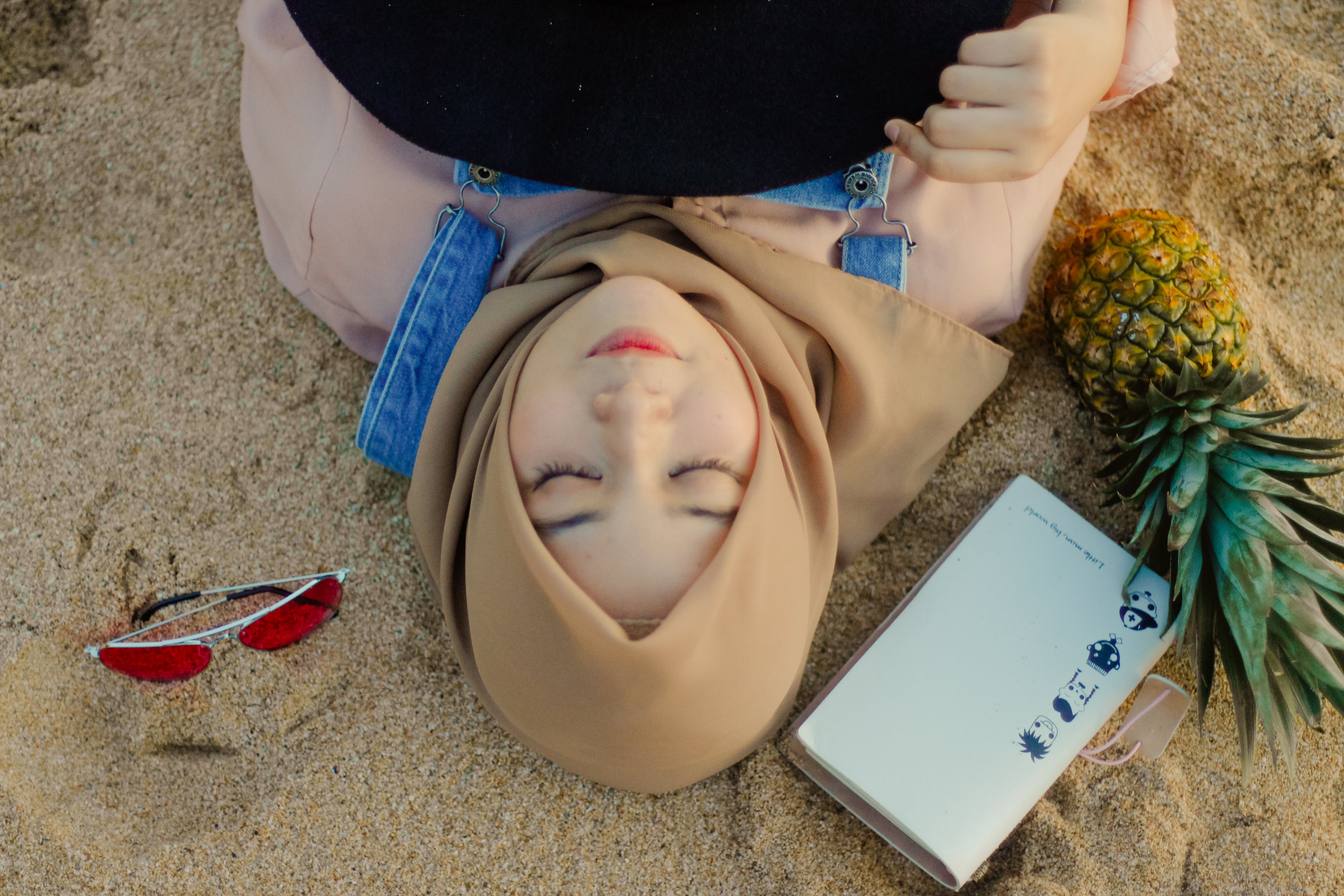 Woman Lying on Sand Beside Sunglasses
