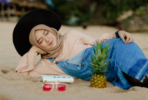 Woman in Blue Denim Dungaree Lying on Sand