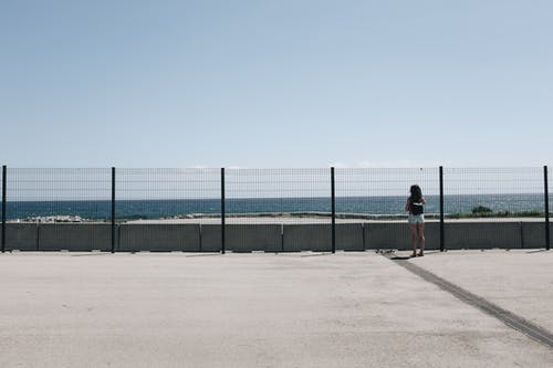 Woman Standing Near Fence and Body of Water