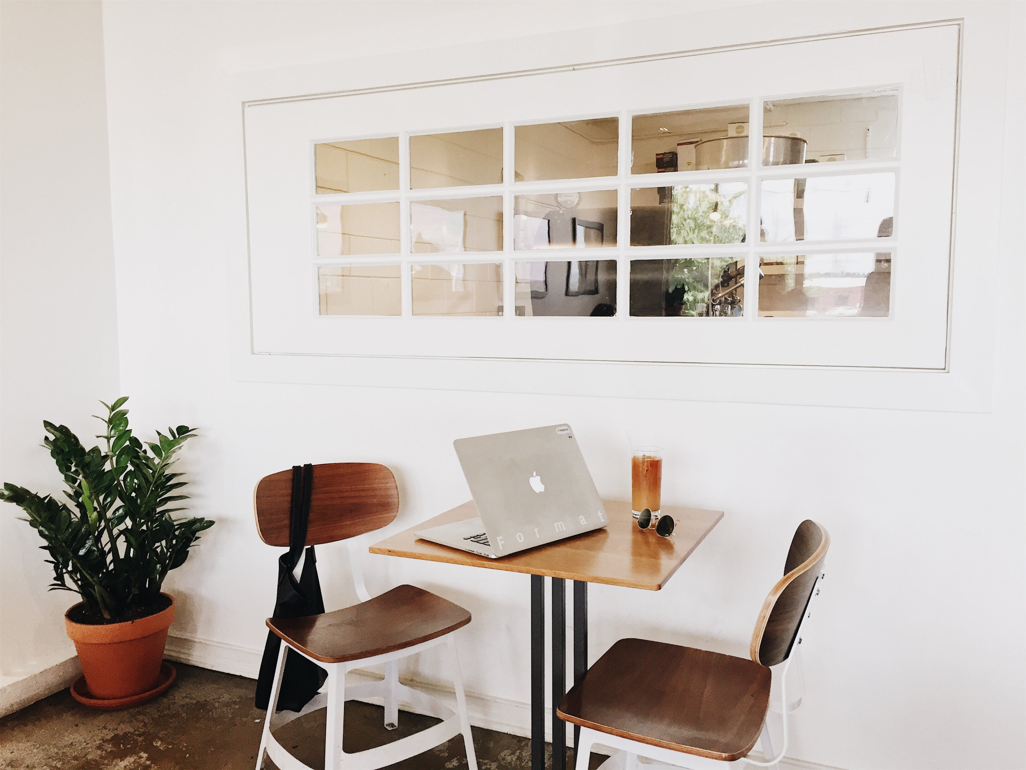 Macbook on Brown Wooden Dining Table and Chairs