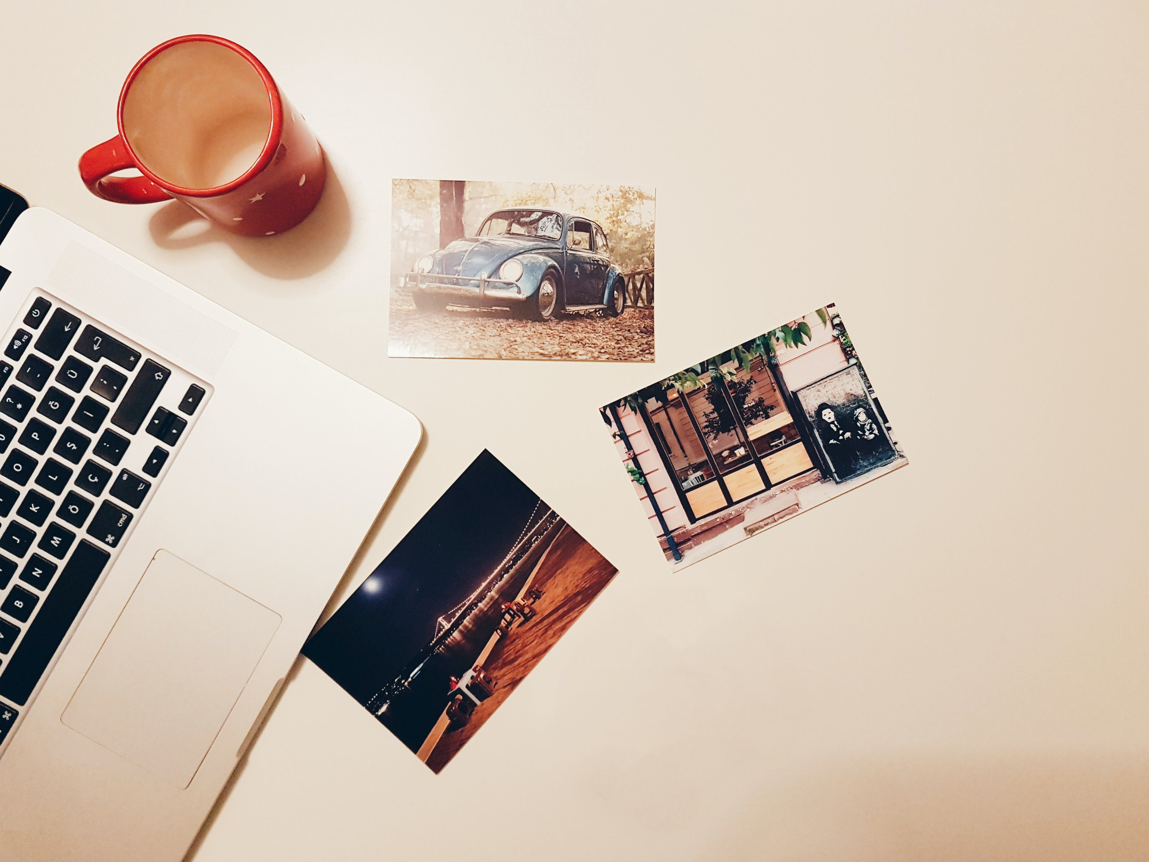 Three Assorted Photos on Desk Beside Laptop and Mug