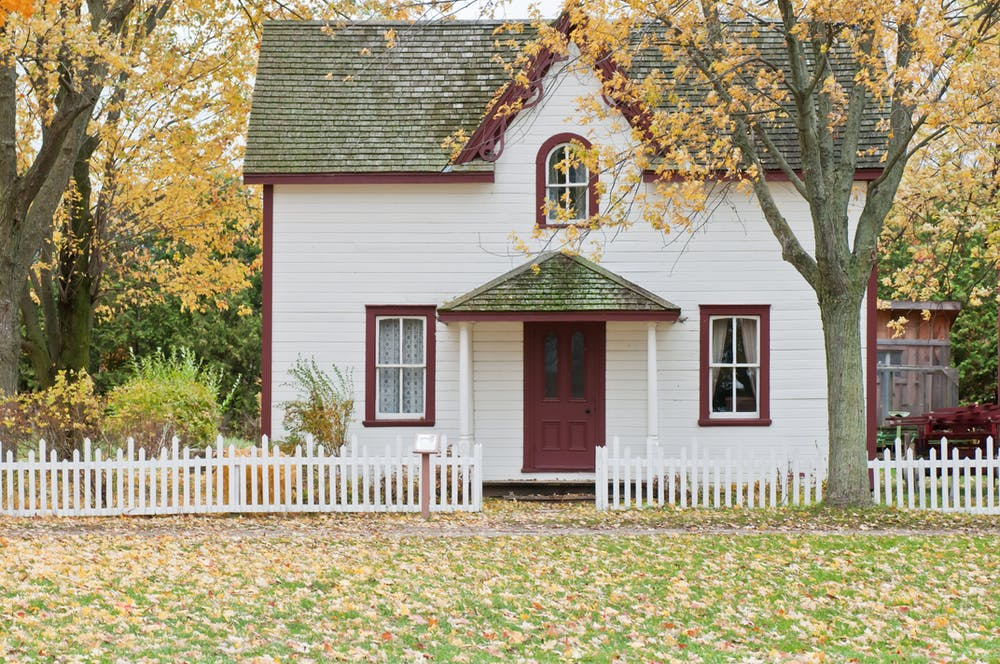 White and red wooden house with fence.   Photo: Pexels