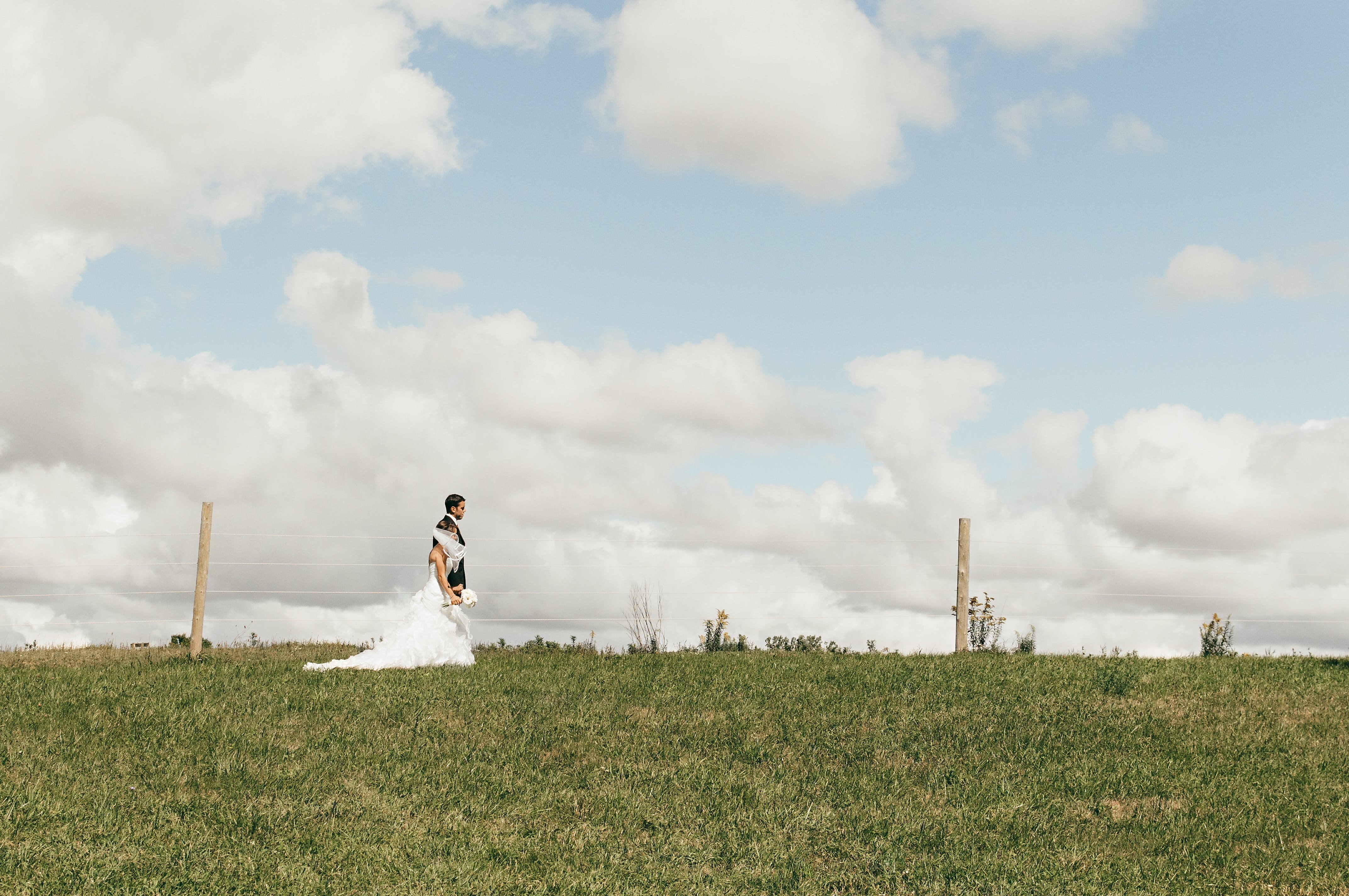 Couple in Wedding Suit and Dress on an Open Fiele