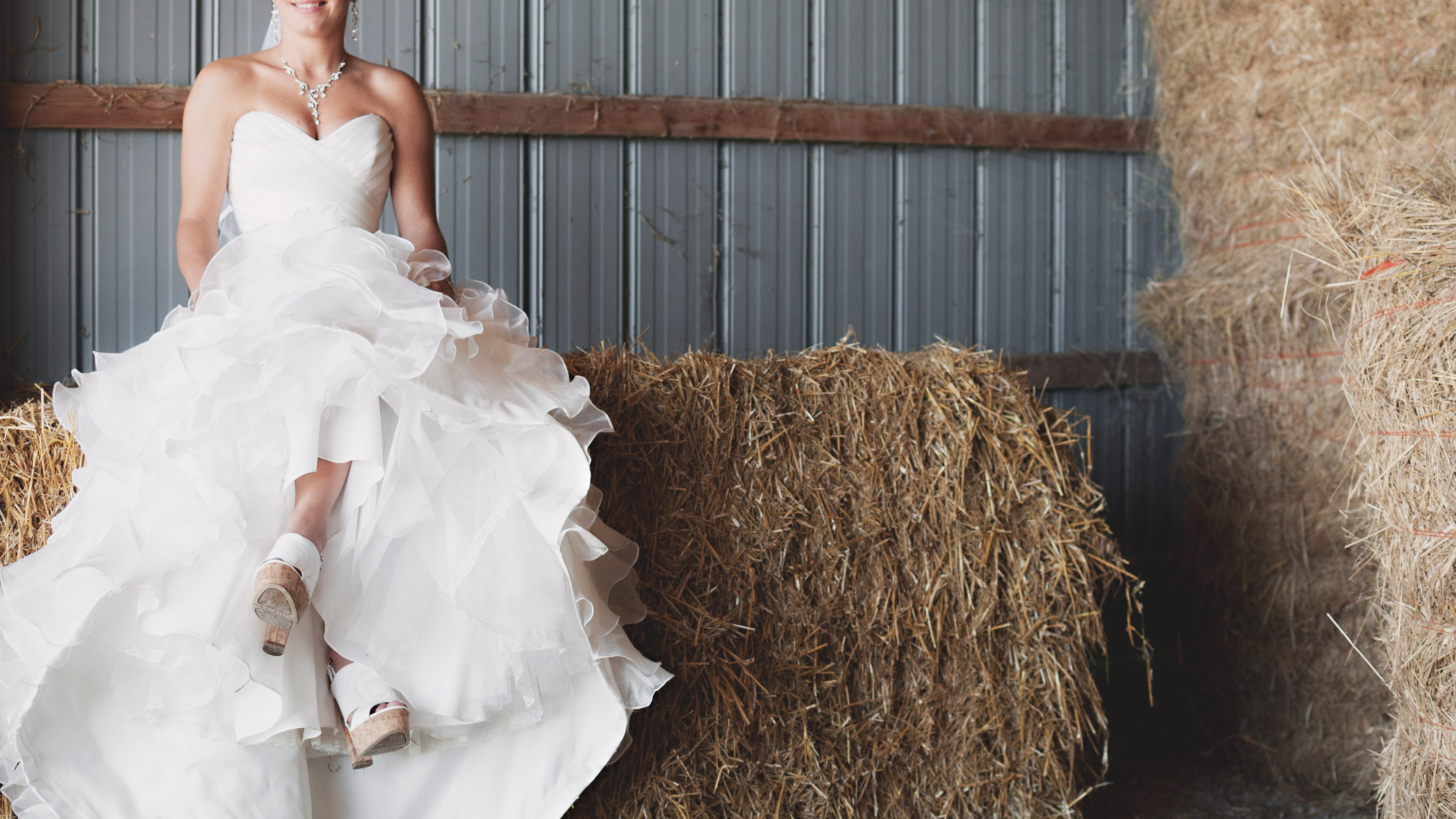 Woman in White Strapless Sweetheart Neckline Bridal Gown Sitting of Brown Hay