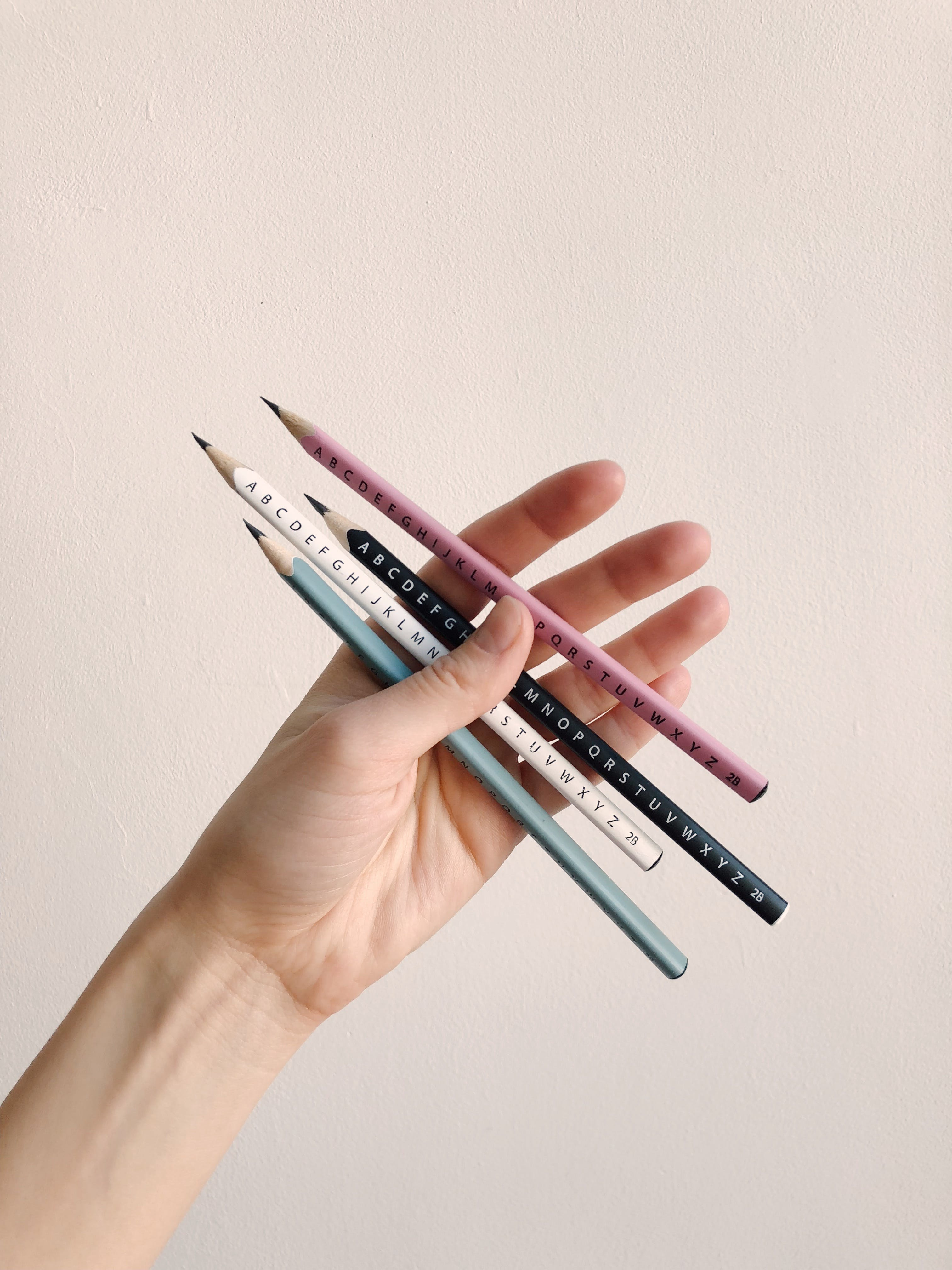 Photo of Person Holding Assorted Pencils
