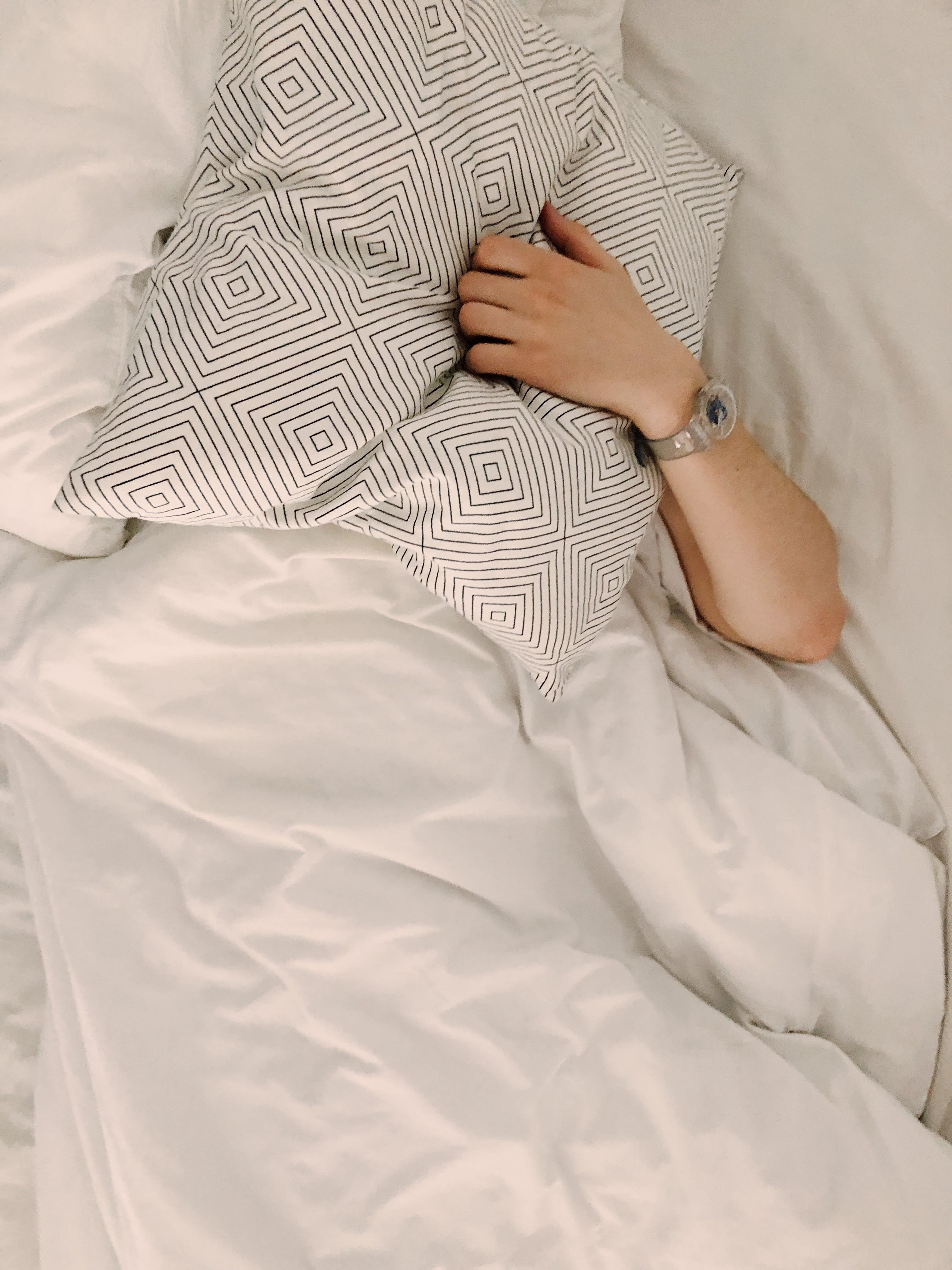 Person Holding Gray and White Throw Pillow