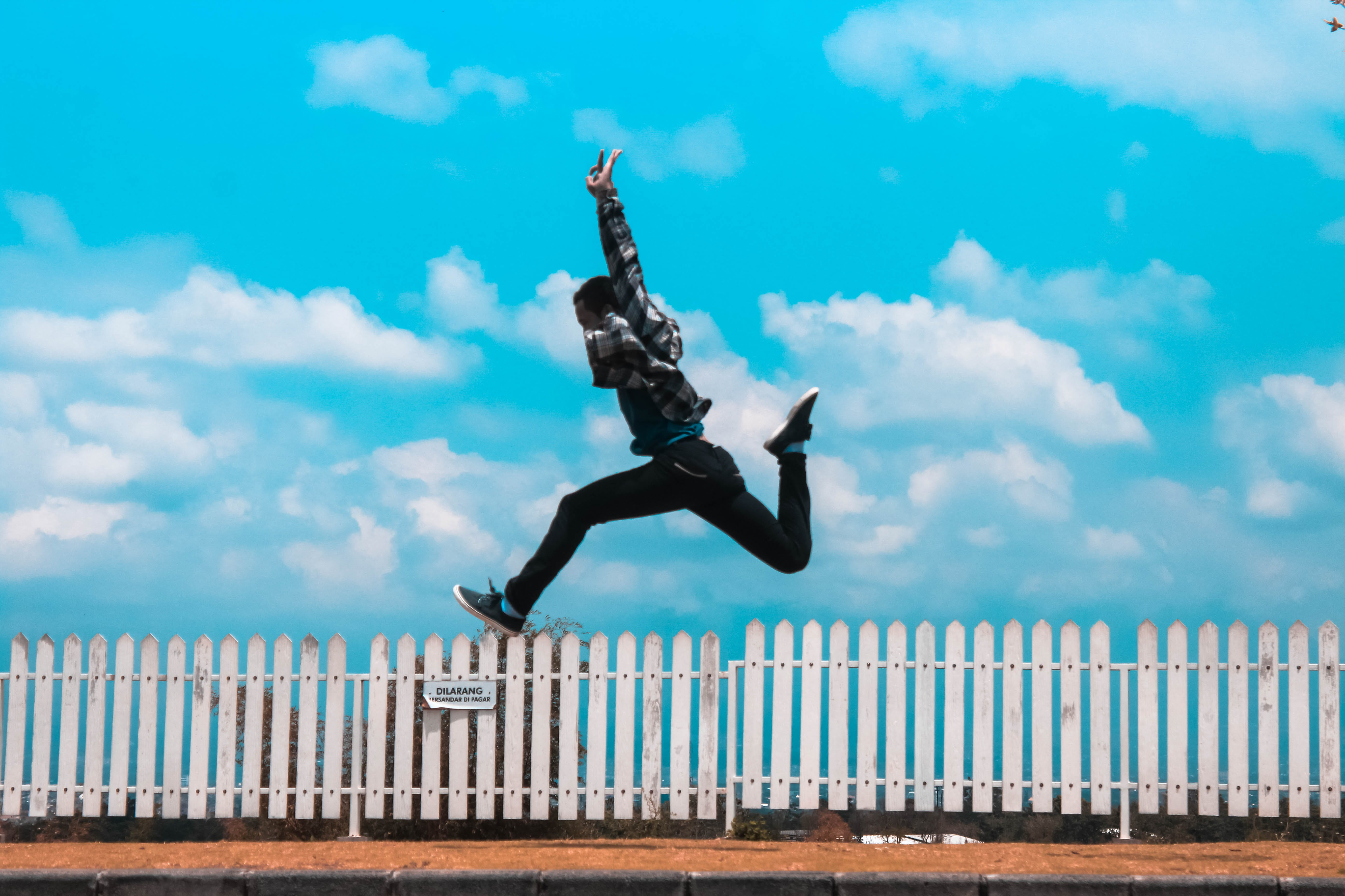 Man Jumping over White Fence