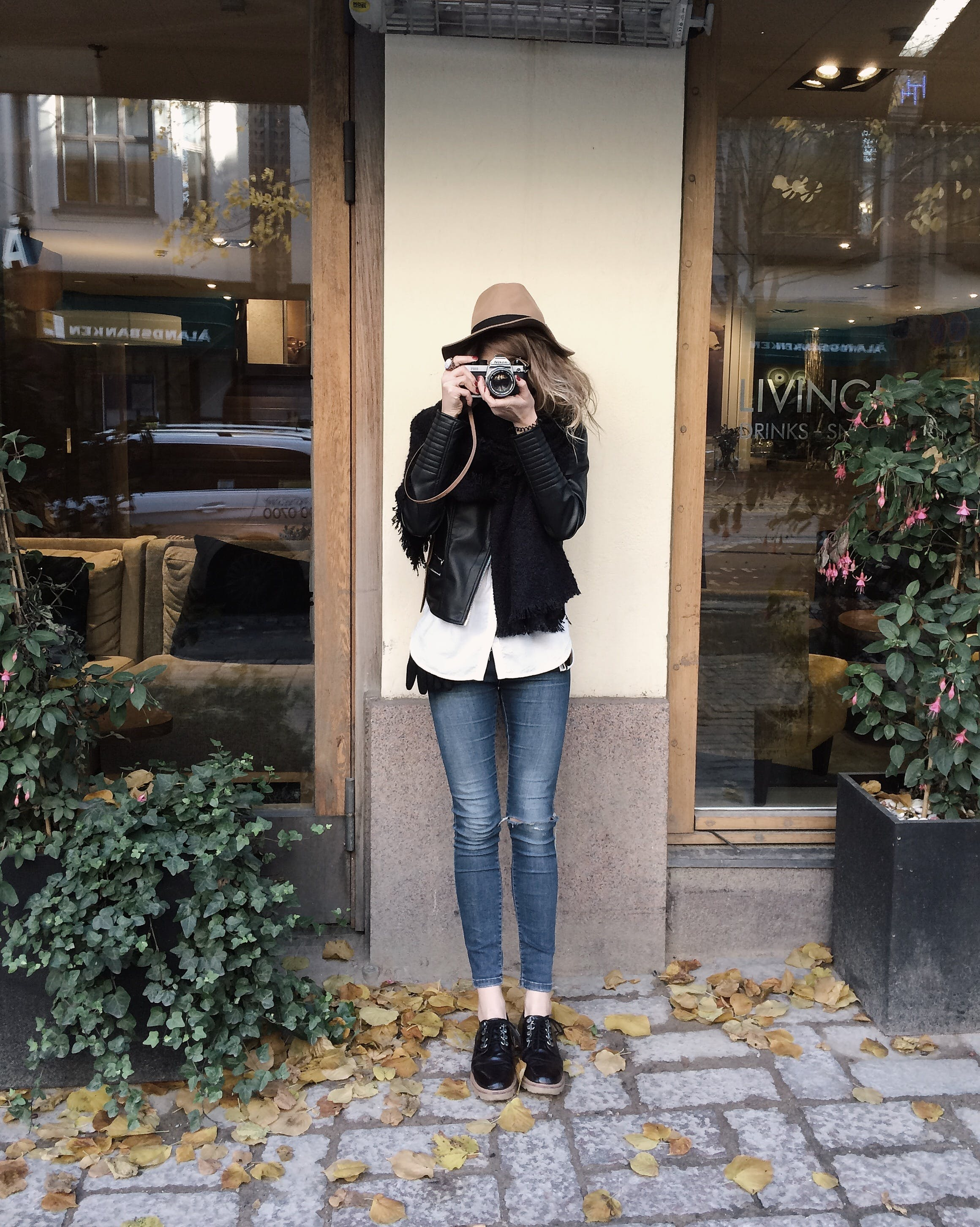 Woman Wearing Black Jacket and Blue Jeans Leaning on Wall