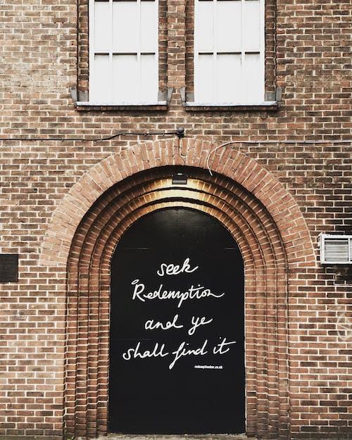 Pintu Kayu Hitam Dengan Kutipan Tercetak Pada Siang Hari
