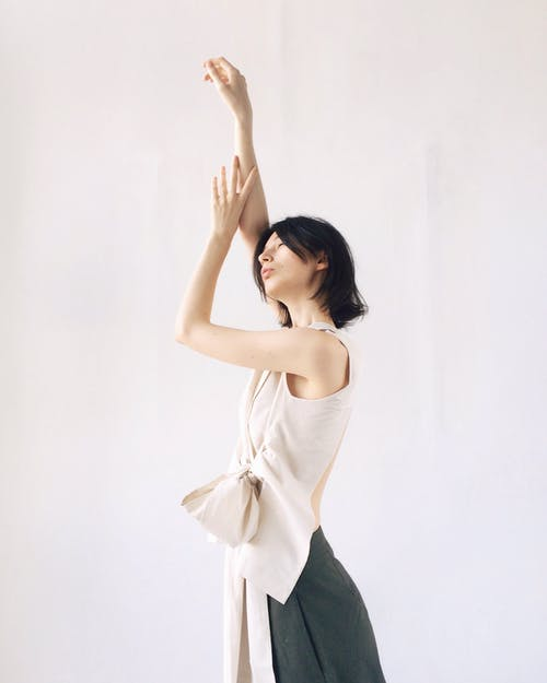 Women's Beige Sleeveless Blouse Raising Hands