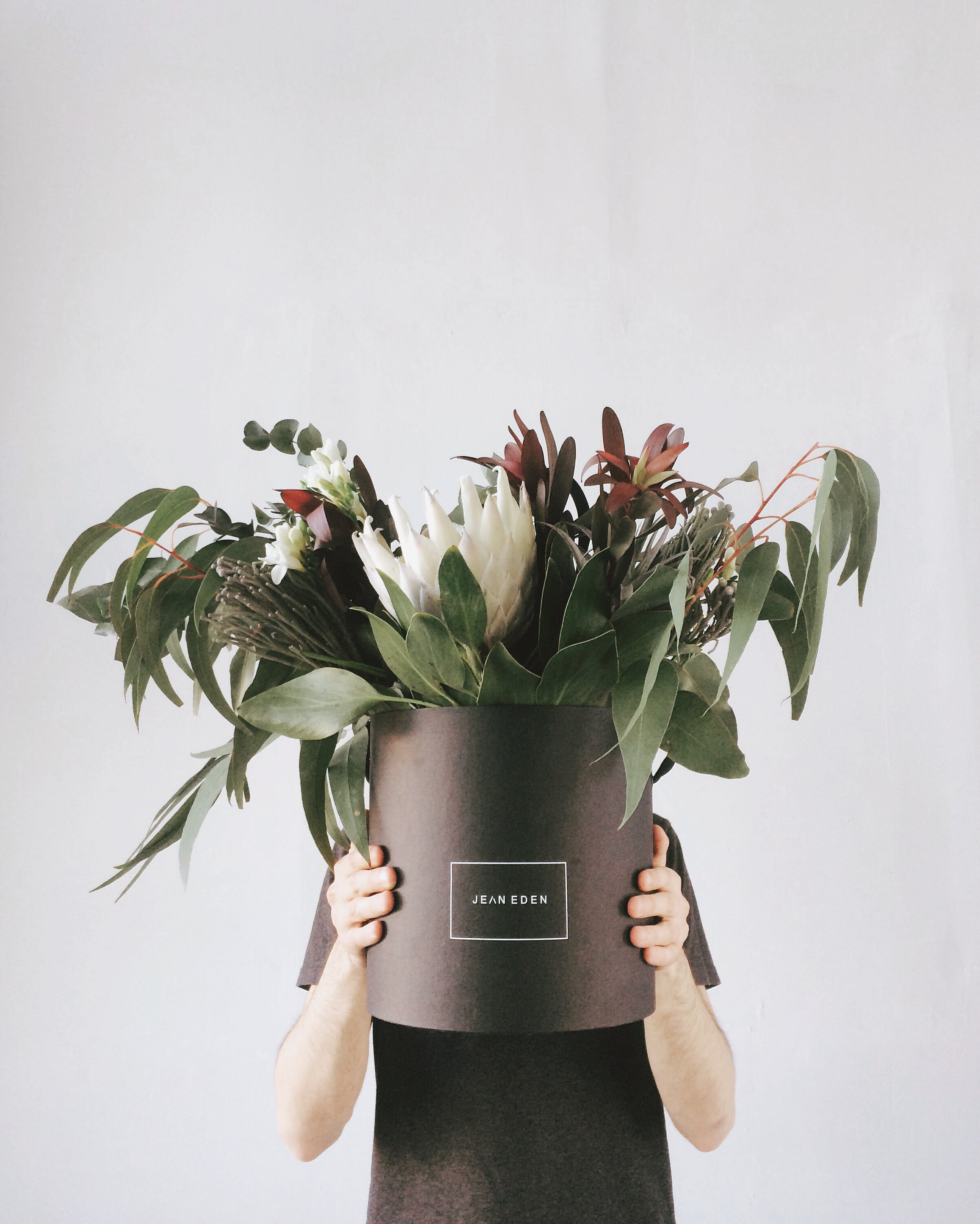 Person in Black T-shirt Holding Potted Flowers