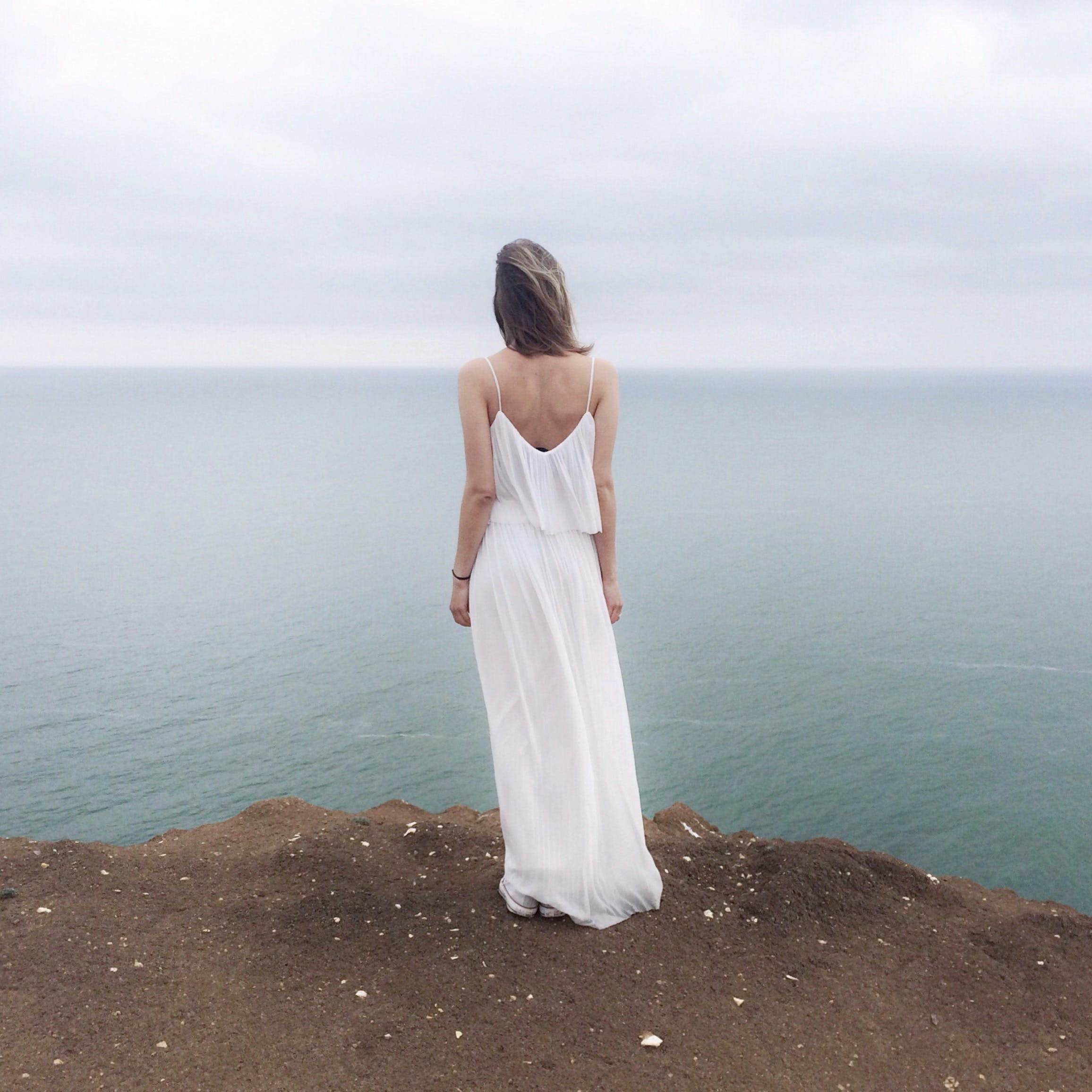 Woman in White Spaghetti Strap Dress Standing on Cliff