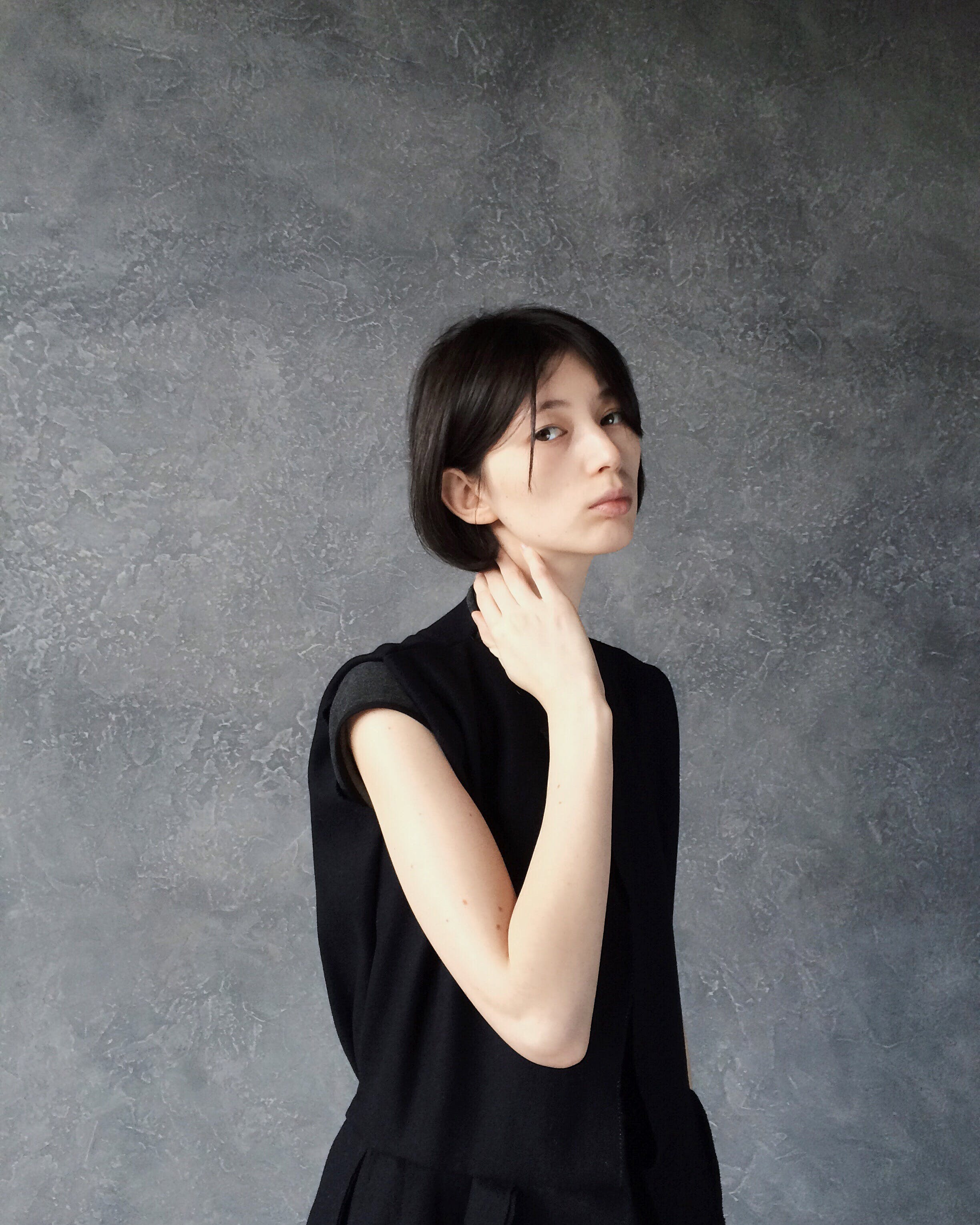 Woman in Black Top Standing Near Gray Wall