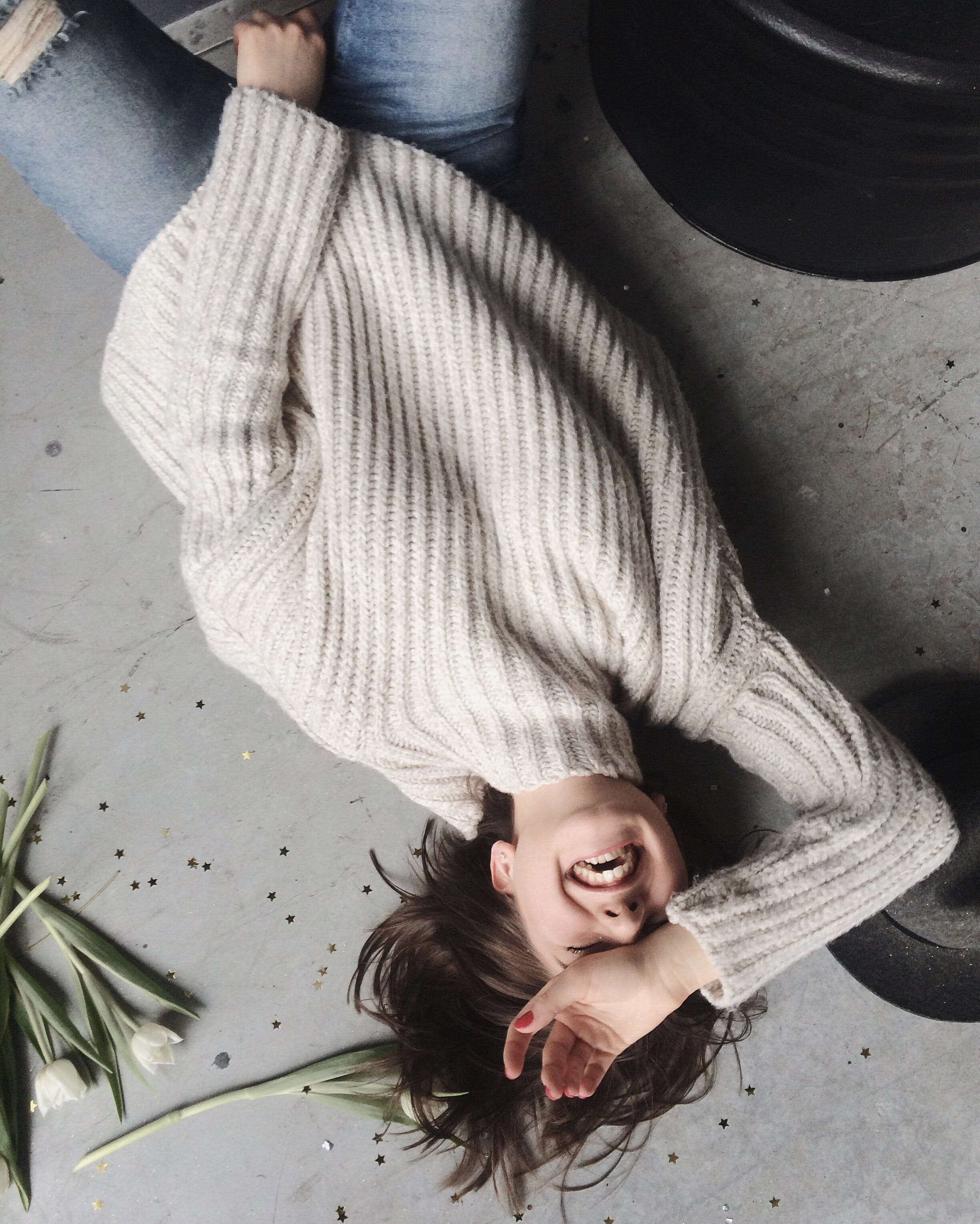 Woman Wearing Gray Sweater Lying on Gray Surface
