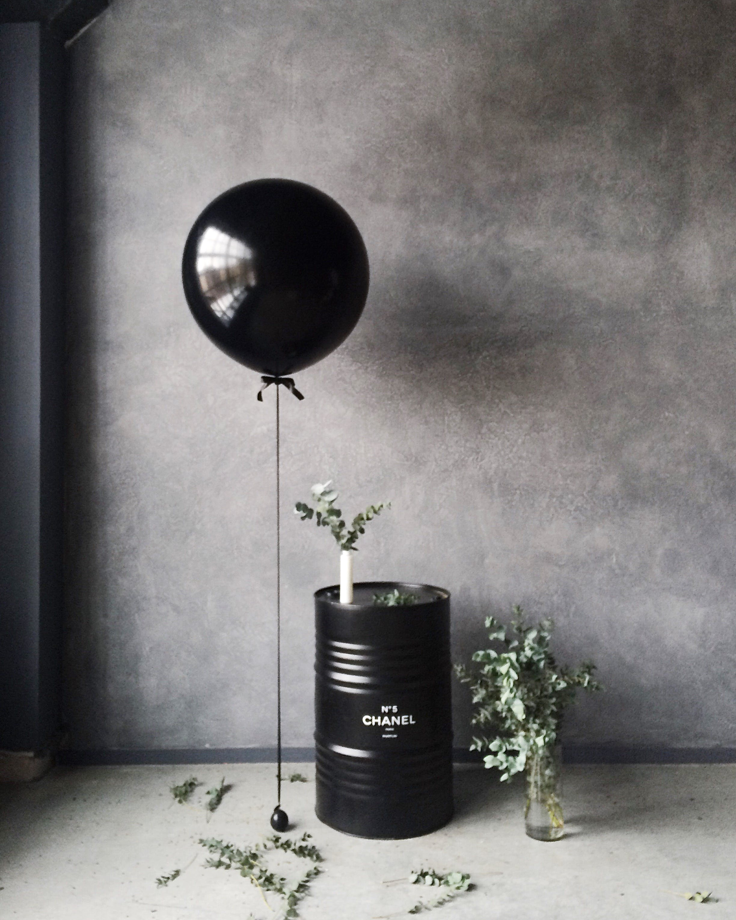 Grayscale Photography of Balloon Beside Chanel Metal Barrel