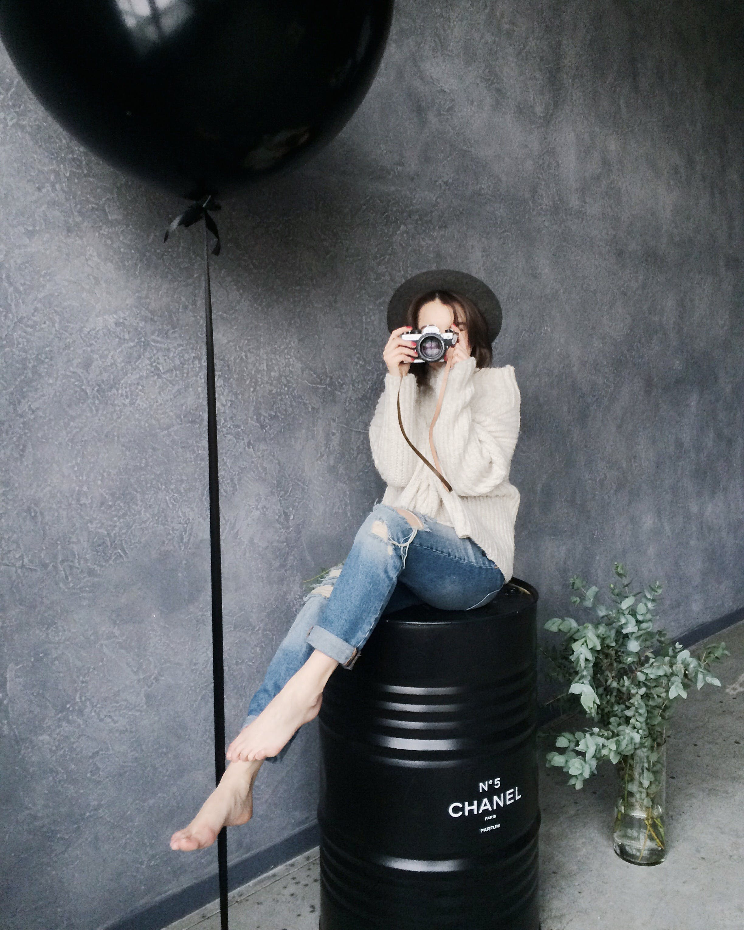 Woman Using Silver Camera Sitting on Black Container Drum