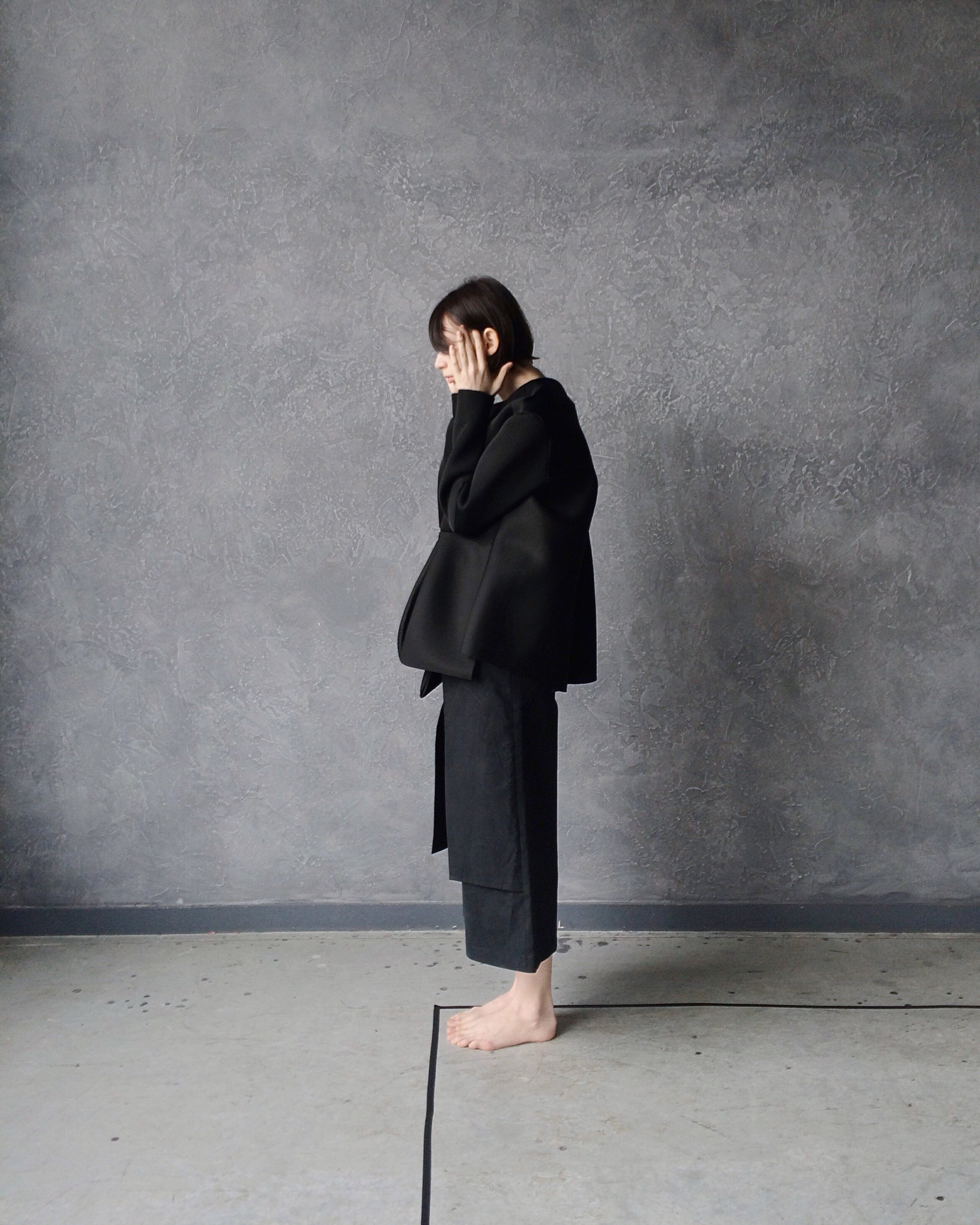 Woman in Black Gi Standing Beside Gray Wall