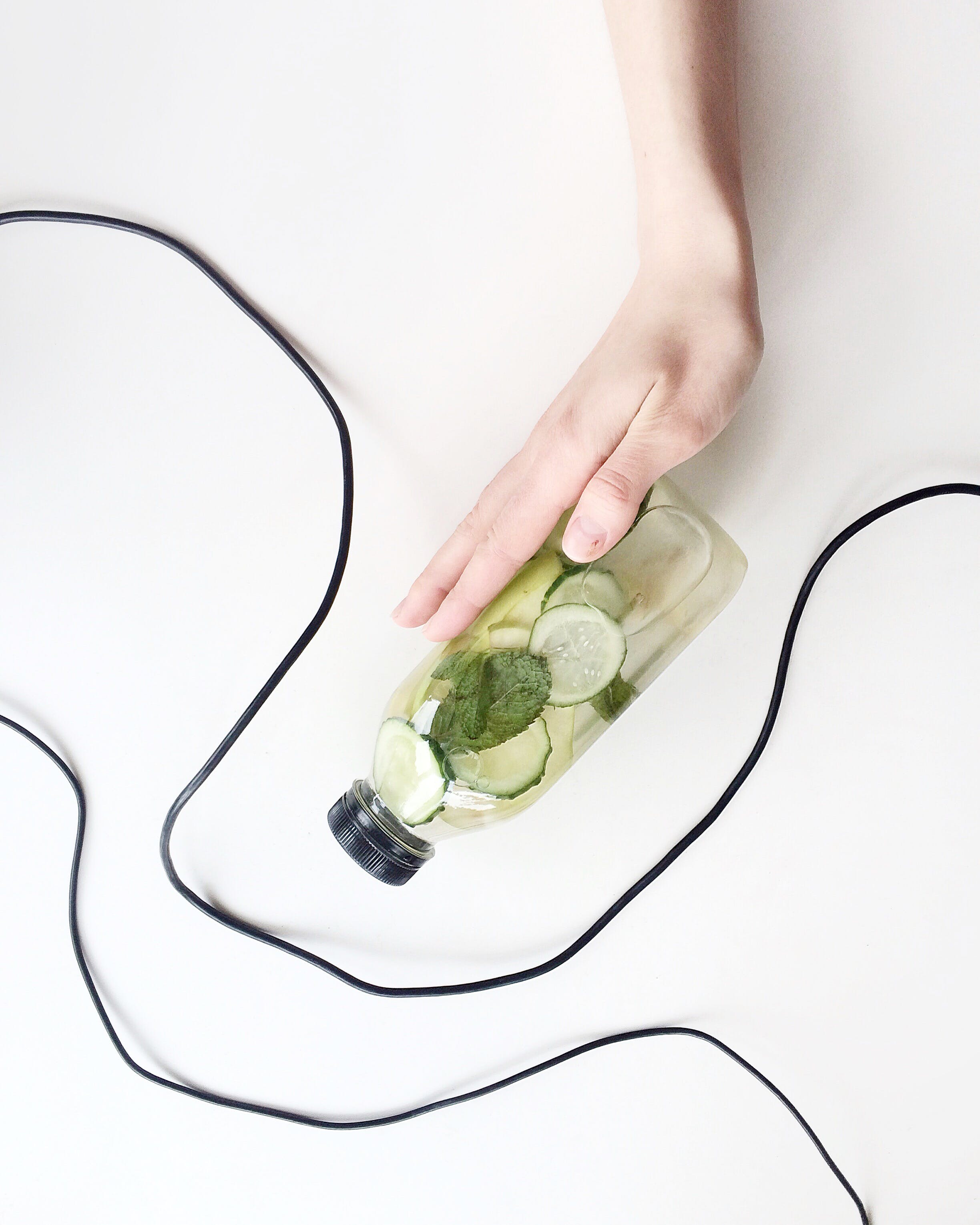 Person Holding Bottle and Cucumber