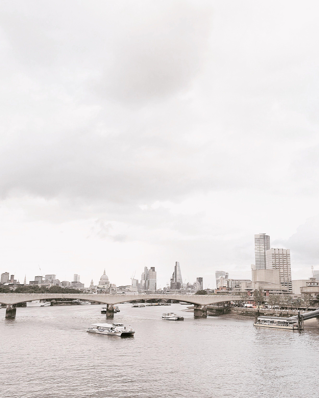 Grayscale Photo of Bridge Near White Boat