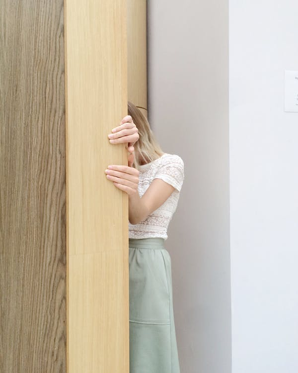 Woman in White Lace Cap-sleeved Top and Green Skirt Hiding Behind Brown Wall