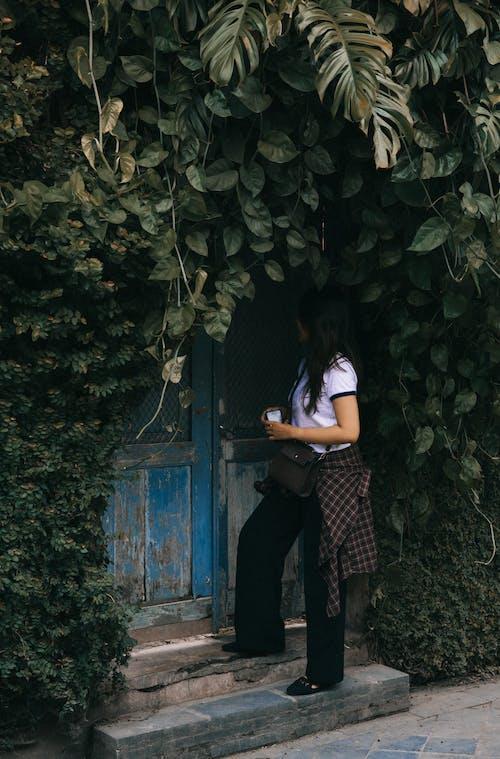 Woman Standing Beside Blue Wooden Door