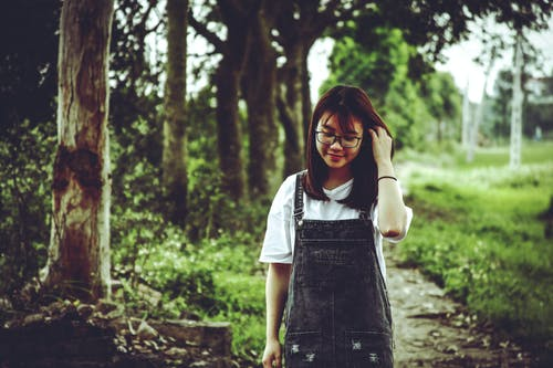 Woman Wearing White V-neck T-shirt and Black Denim Dungaree Standing Beside Trees