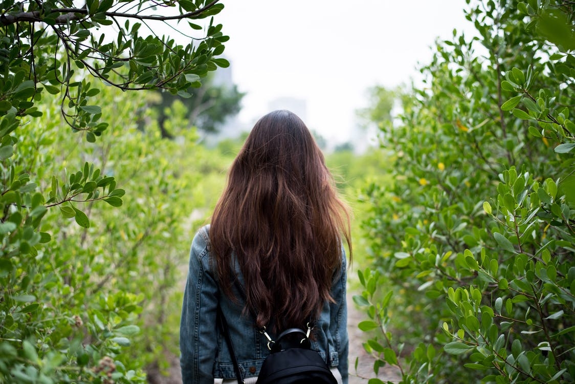 Woman in Gray Denim Jacket in the Middle of Bushes