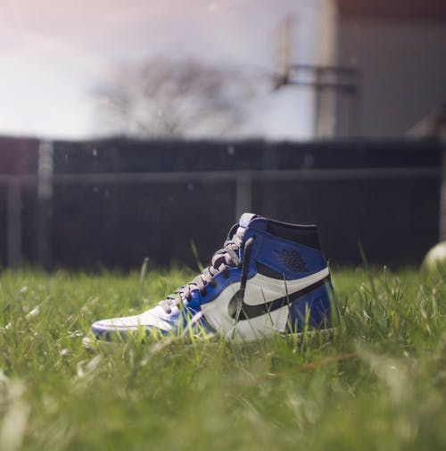 Selective Focus Photography of Air Jordan 1 On Grass