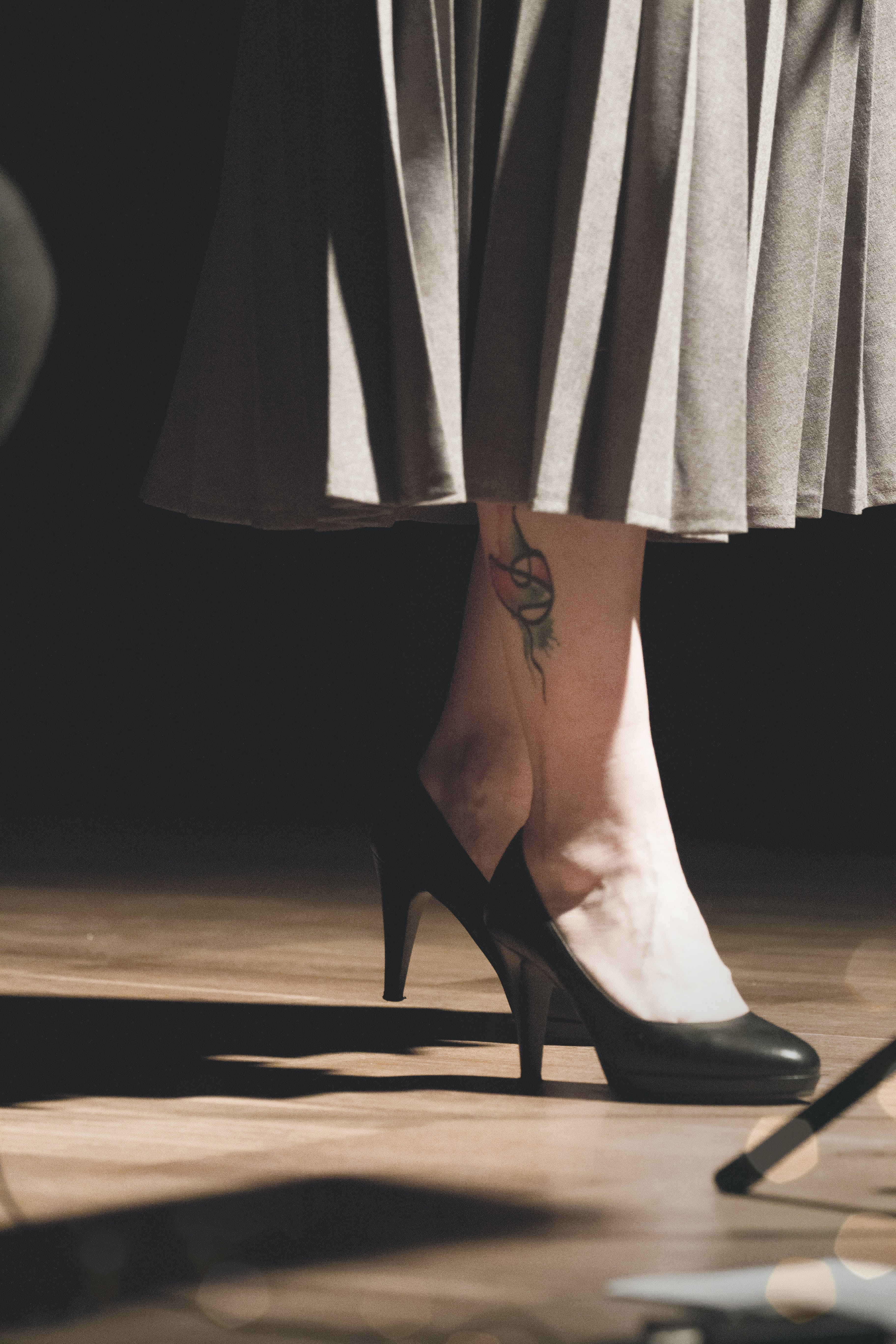 Woman in Black Heeled Shoes Standing on Brown Surface