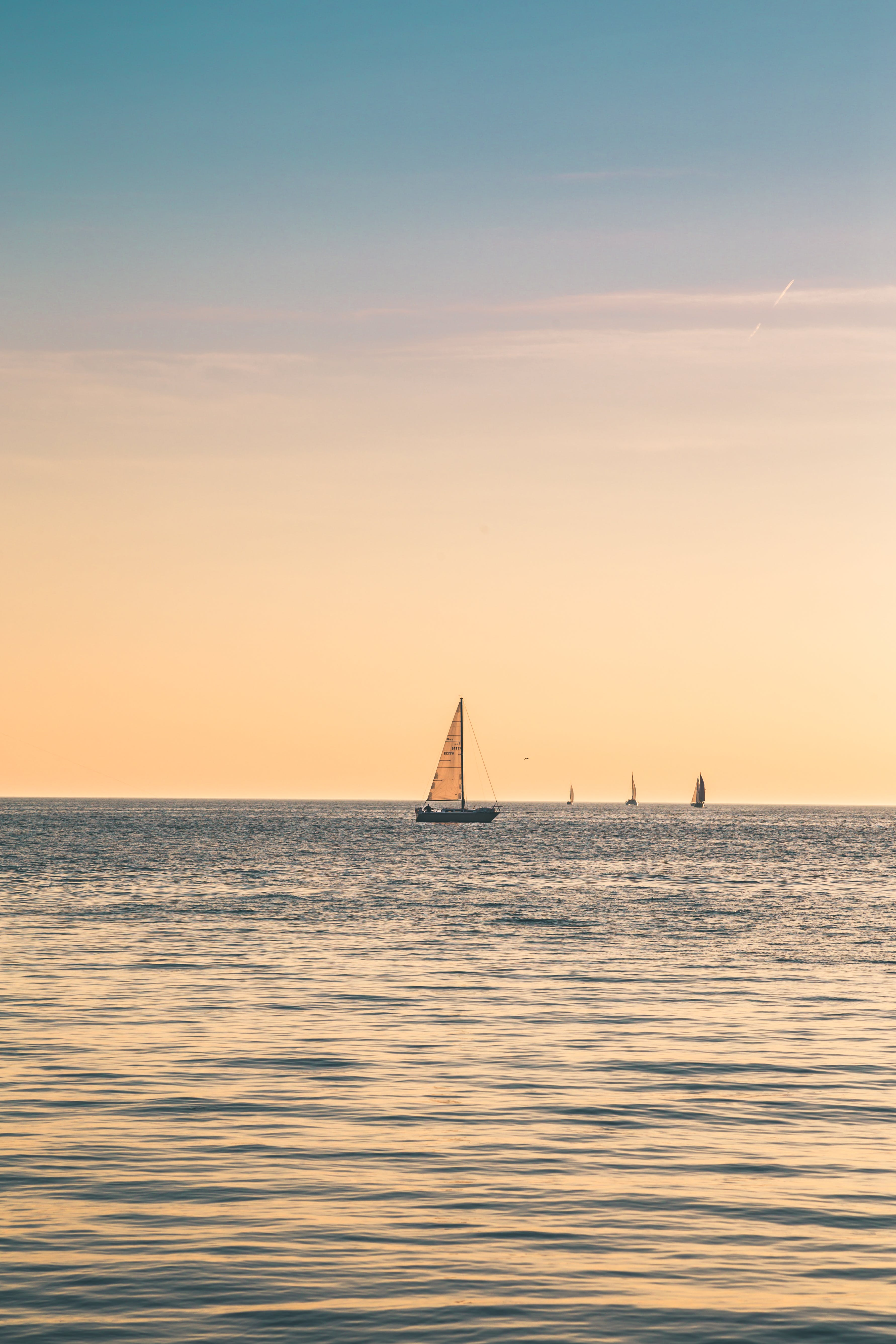 Beige Sailboat Under Clear Skies