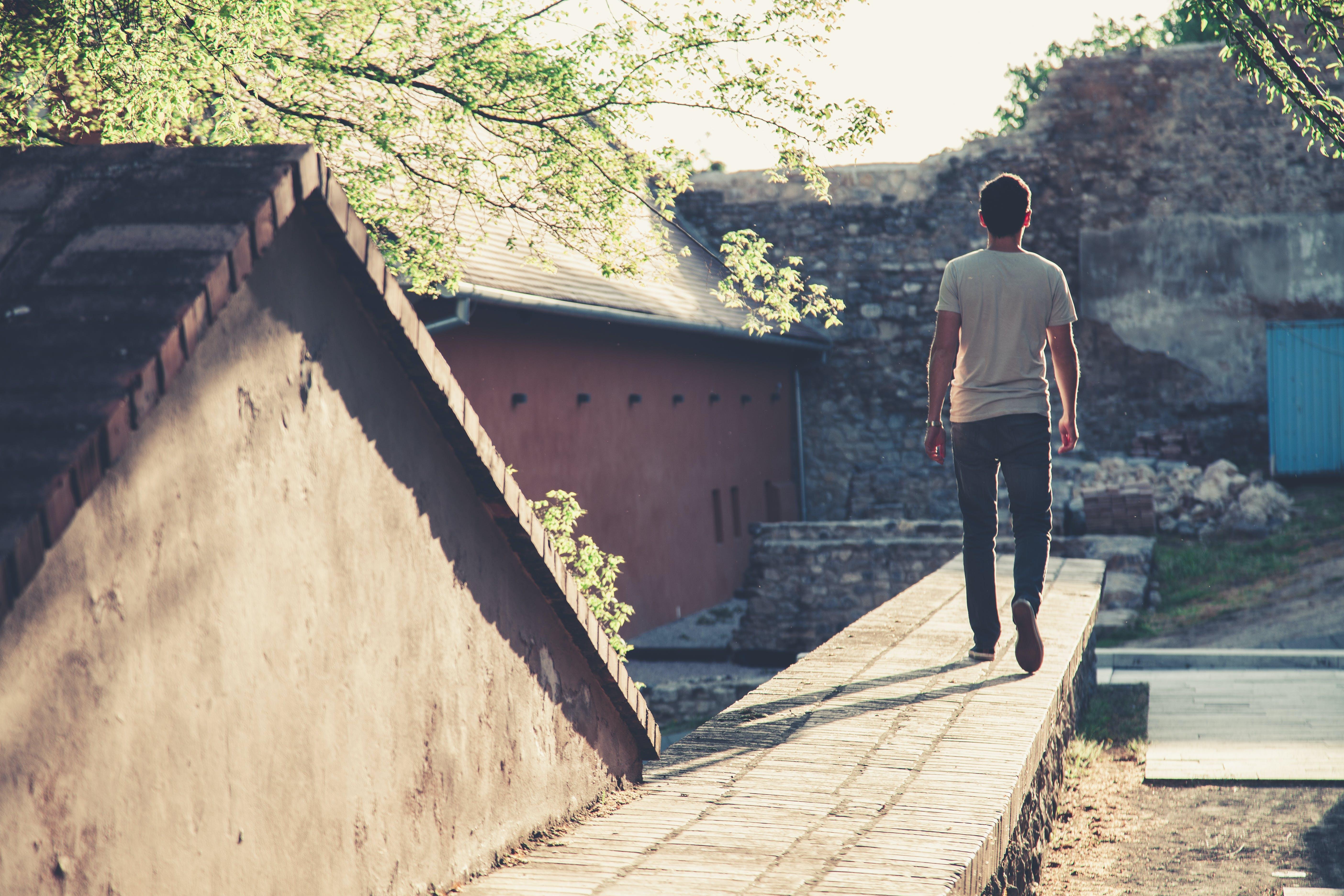 Man Wearing Gray T-shirt and Black Denim Jeans Walking Towards Gray Concrete Pathway