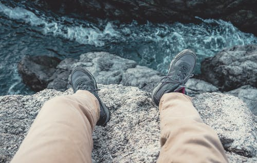 Photo of Man Sitting on the Cliff