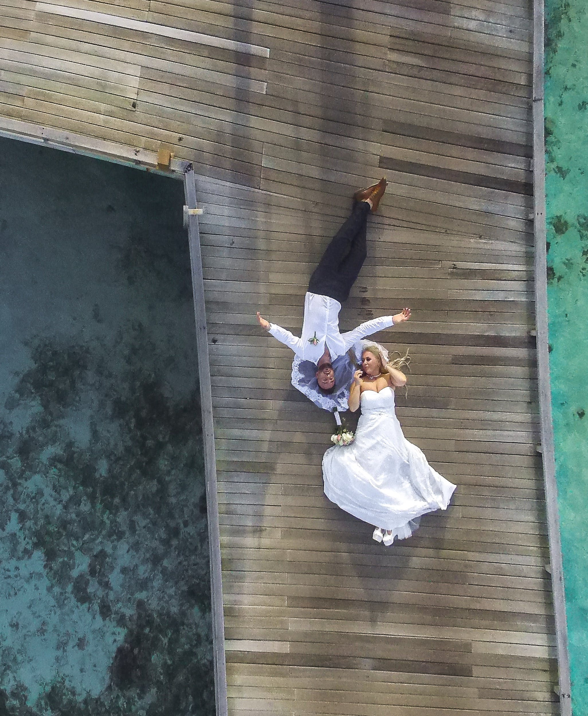 Photo of Bride and Groom Laying on Pier
