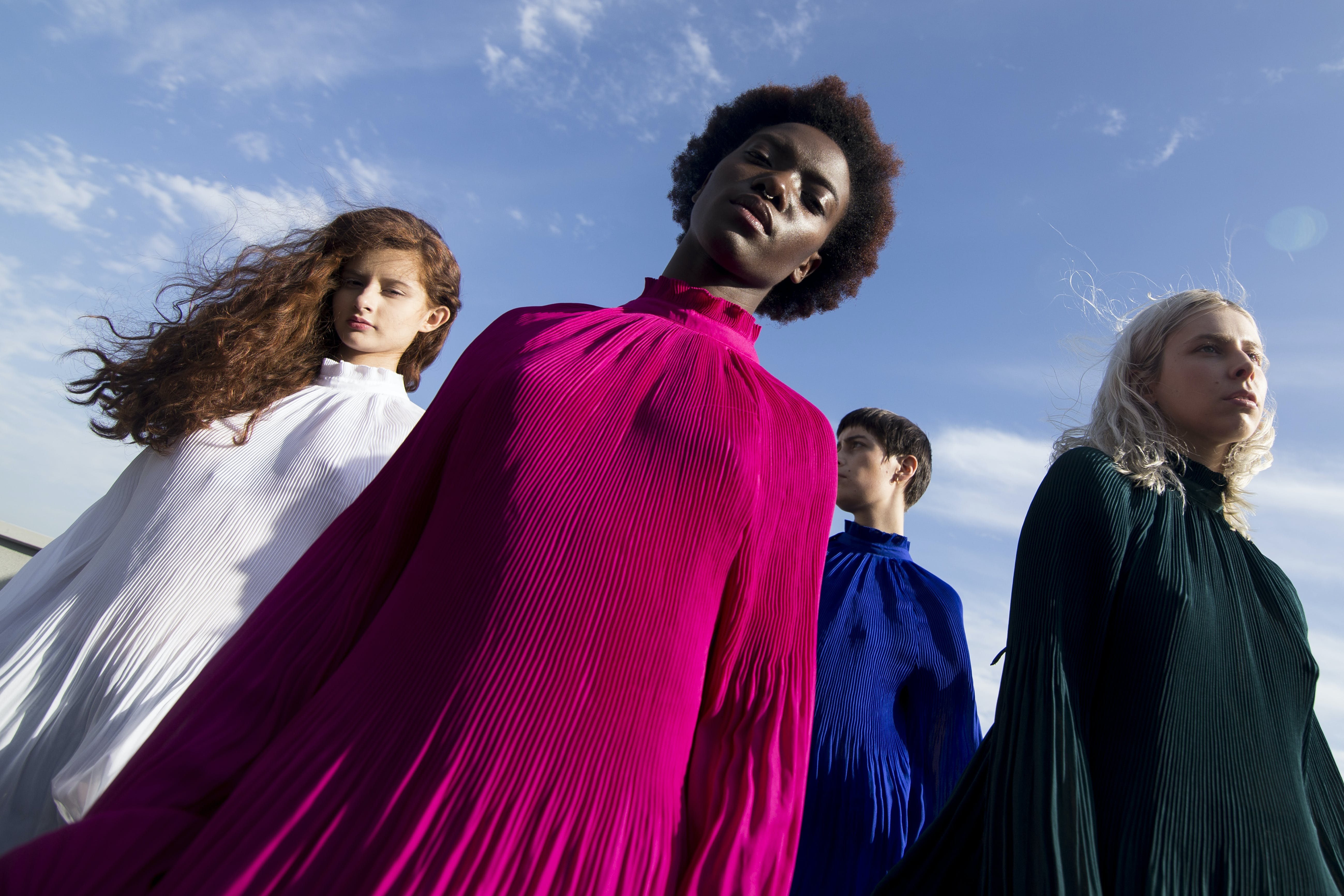 Low-angle Photography of Four Women in Assorted-color Long-sleeved Turtle-neck Dresses